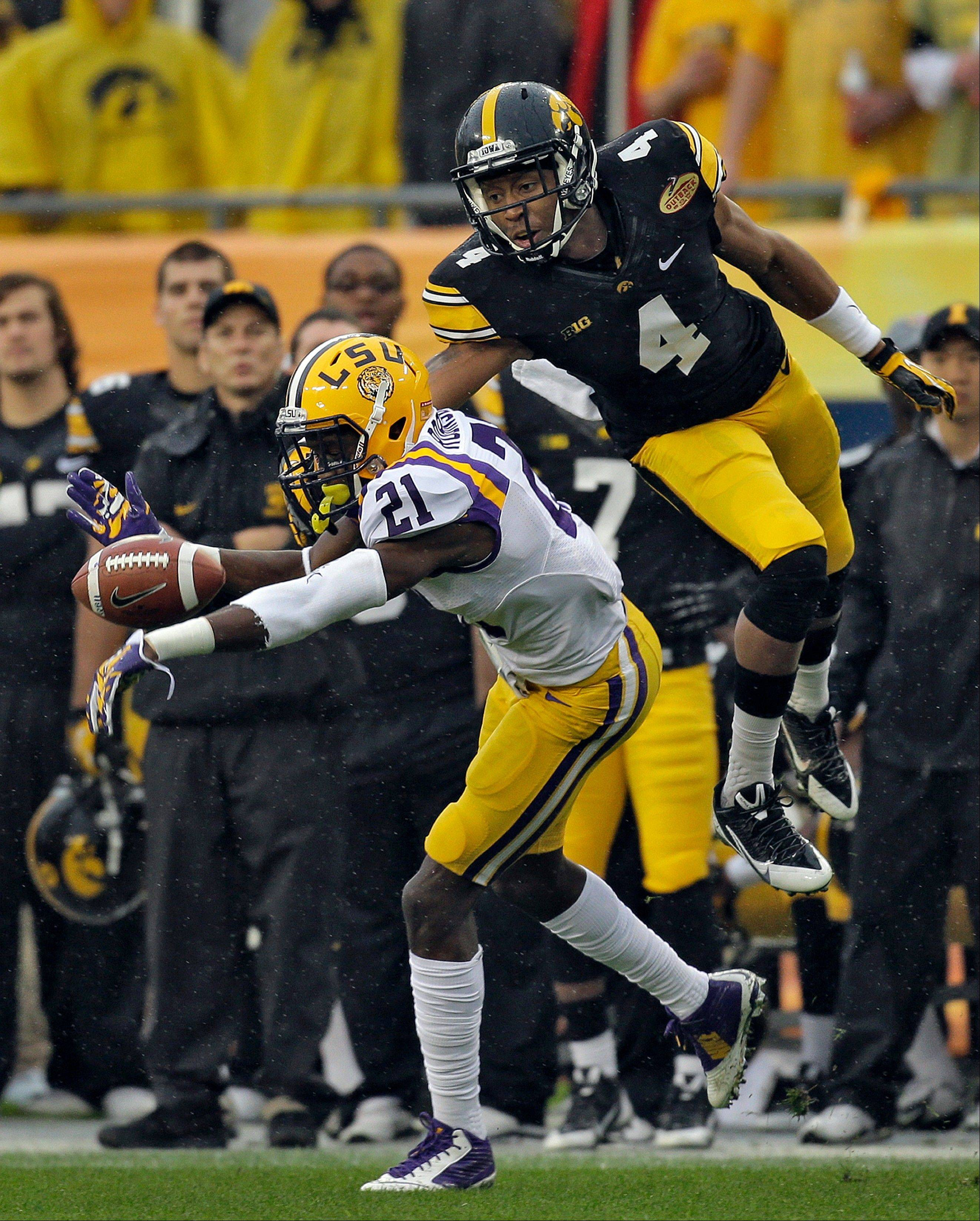 LSU defensive back Rashard Robinson (21) knocks a pass away from Iowa wide receiver Tevaun Smith (4) during the first quarter of the Outback Bowl NCAA college football game Wednesday, Jan. 1, 2014, in Tampa, Fla.