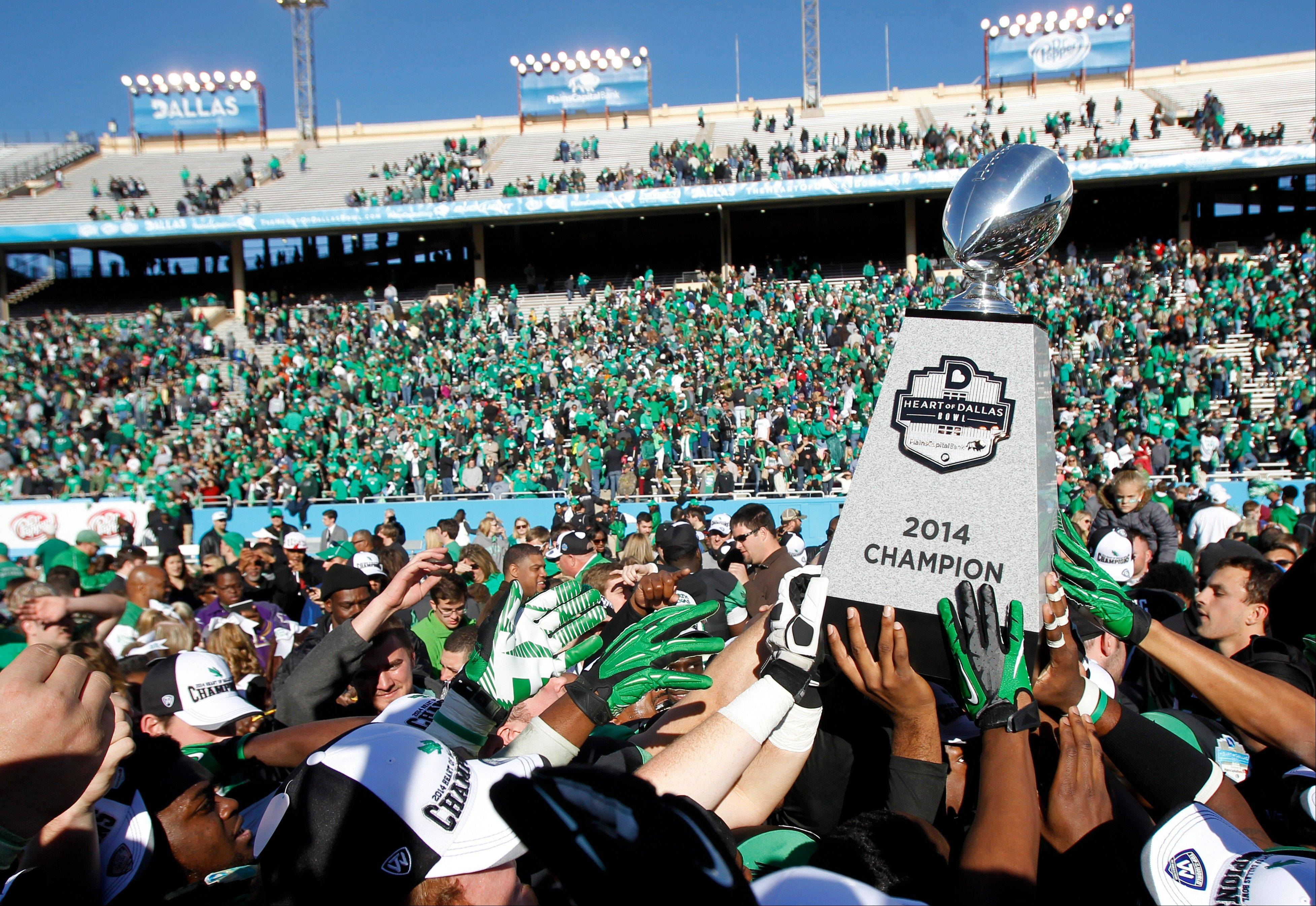 North Texas players hold aloft the Heart of Dallas Bowl trophy following their 36-14 win over UNLV in the Heart of Dallas NCAA college football game, Wednesday, Jan. 1, 2014, in Dallas.