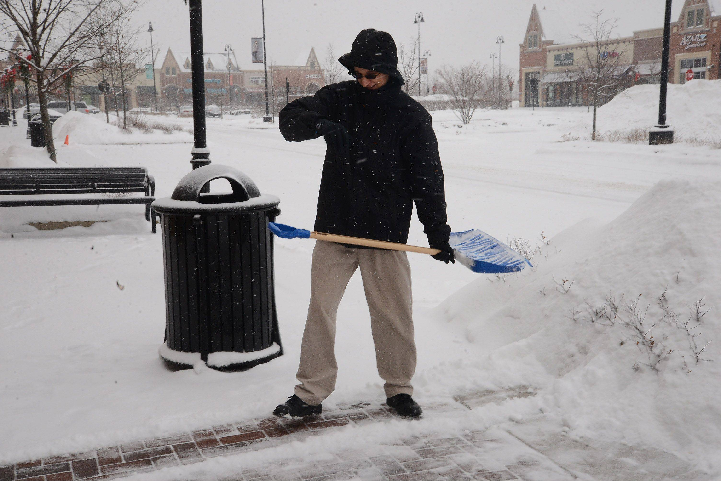 Ryan Courtney shovels Wednesday outside of Go! Calendars Games and Toys at The Arboretum in South Barrington.