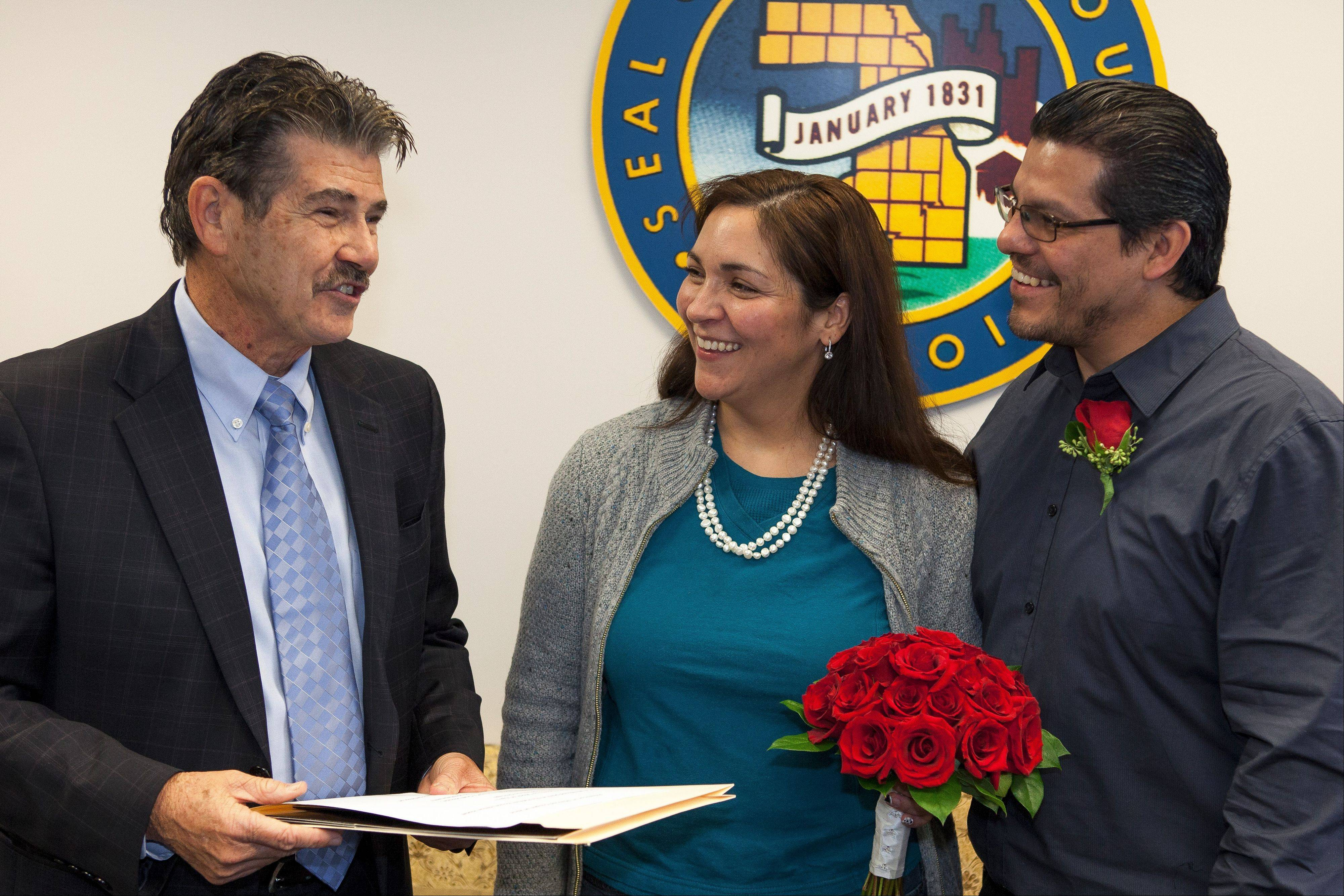 Courtesy of Cook County Clerk�s office Cook County Clerk David Orr marries Ricca Rivera and Fernando Chaidez of Chicago, the first couple wed in the county in 2014.