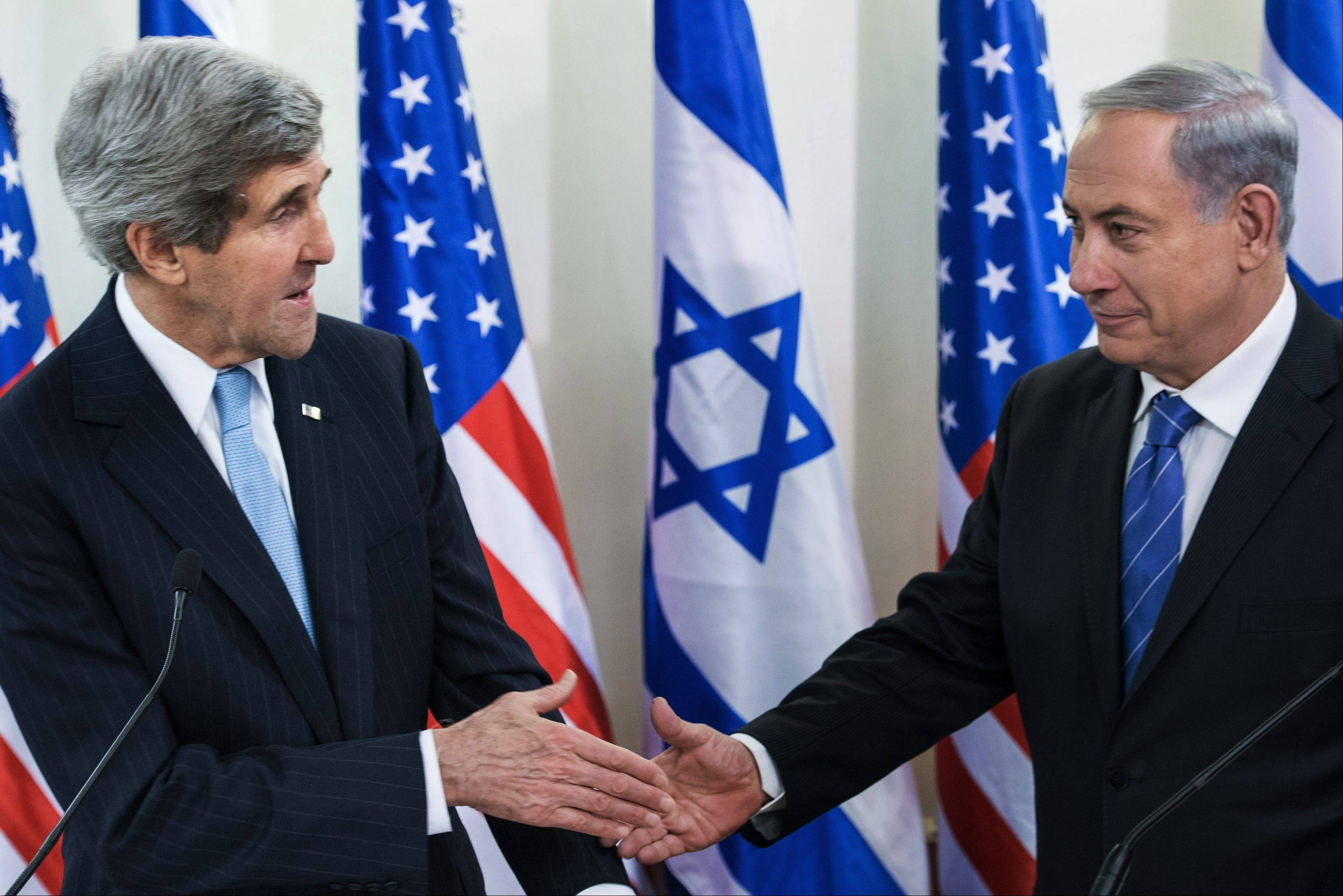 Secretary of State John Kerry, left, and Israeli Prime Minister Benjamin Netanyahu shake hands before a meeting at the prime minister�s office in Jerusalem Thursday. Kerry arrived in Israel to broker Mideast peace talks that are entering a difficult phase aimed at reaching a two-state solution between the Israelis and Palestinians.