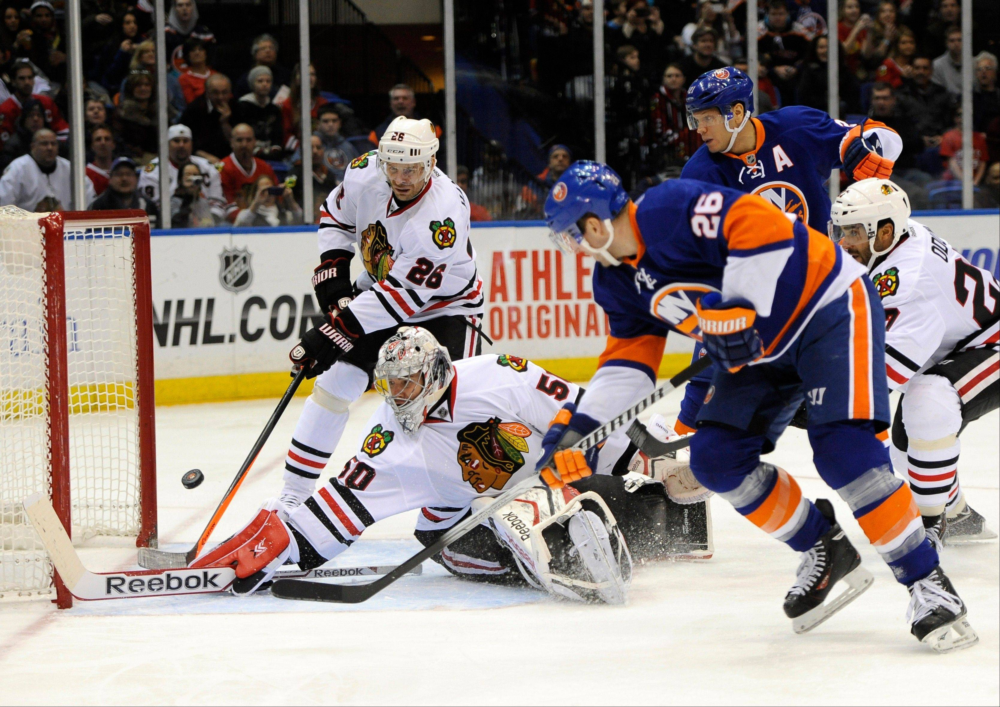 New York Islanders' Thomas Vanek, front right, shoots the puck past Chicago Blackhawks goalie Corey Crawford (50) as Blackhawks' Michal Handzus, back left, tries to defend in the second period of an NHL hockey game on Thursday, Jan. 2, 2014, in Uniondale, N.Y. (AP Photo/Kathy Kmonicek)