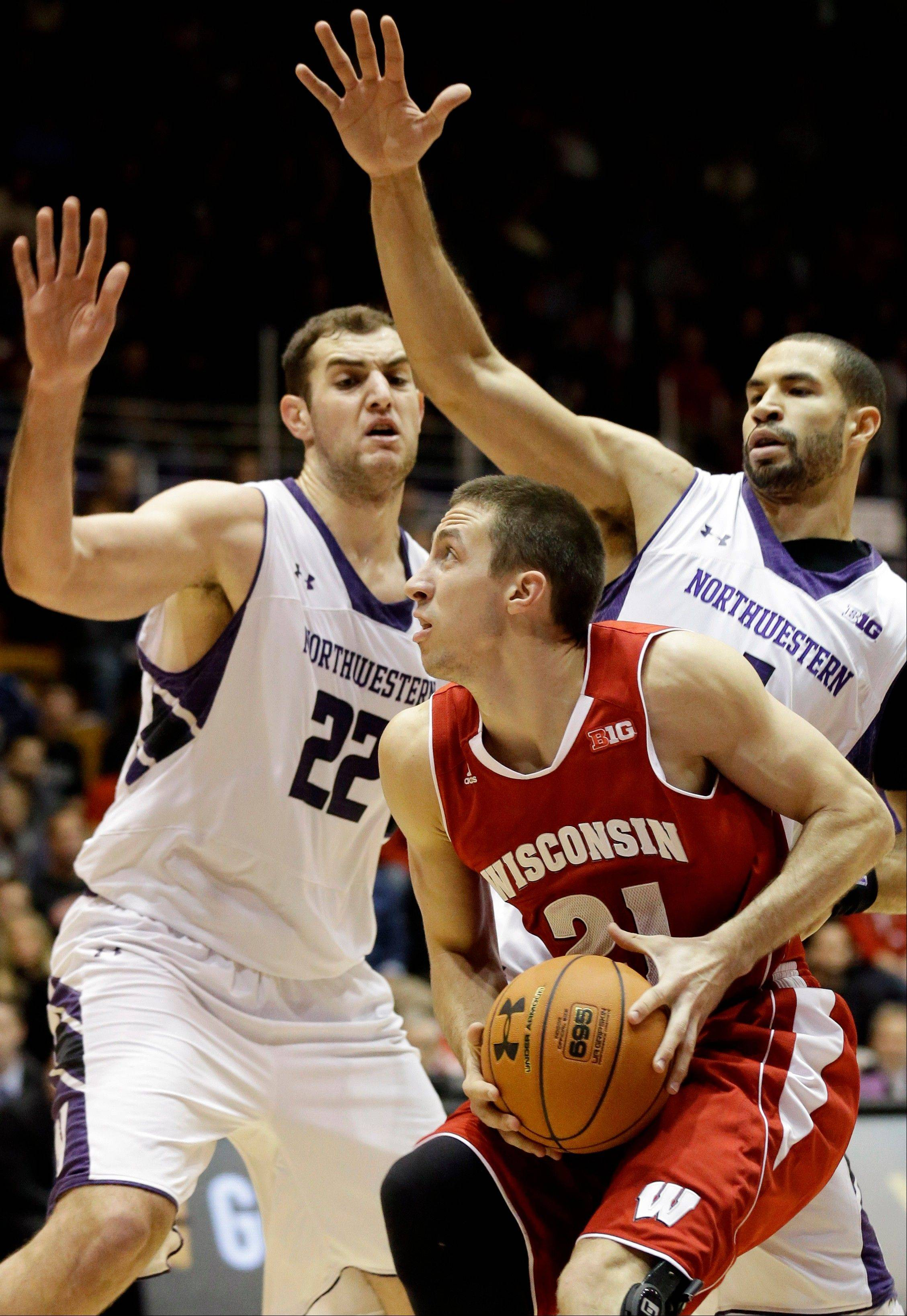 Wisconsin's Josh Gasser (21) looks to the basket as Northwestern center Alex Olah (22) and guard Drew Crawford, left, defend during the first half of an NCAA college basketball game in Evanston, Ill., on Thursday, Jan. 2, 2014. (AP Photo/Nam Y. Huh)