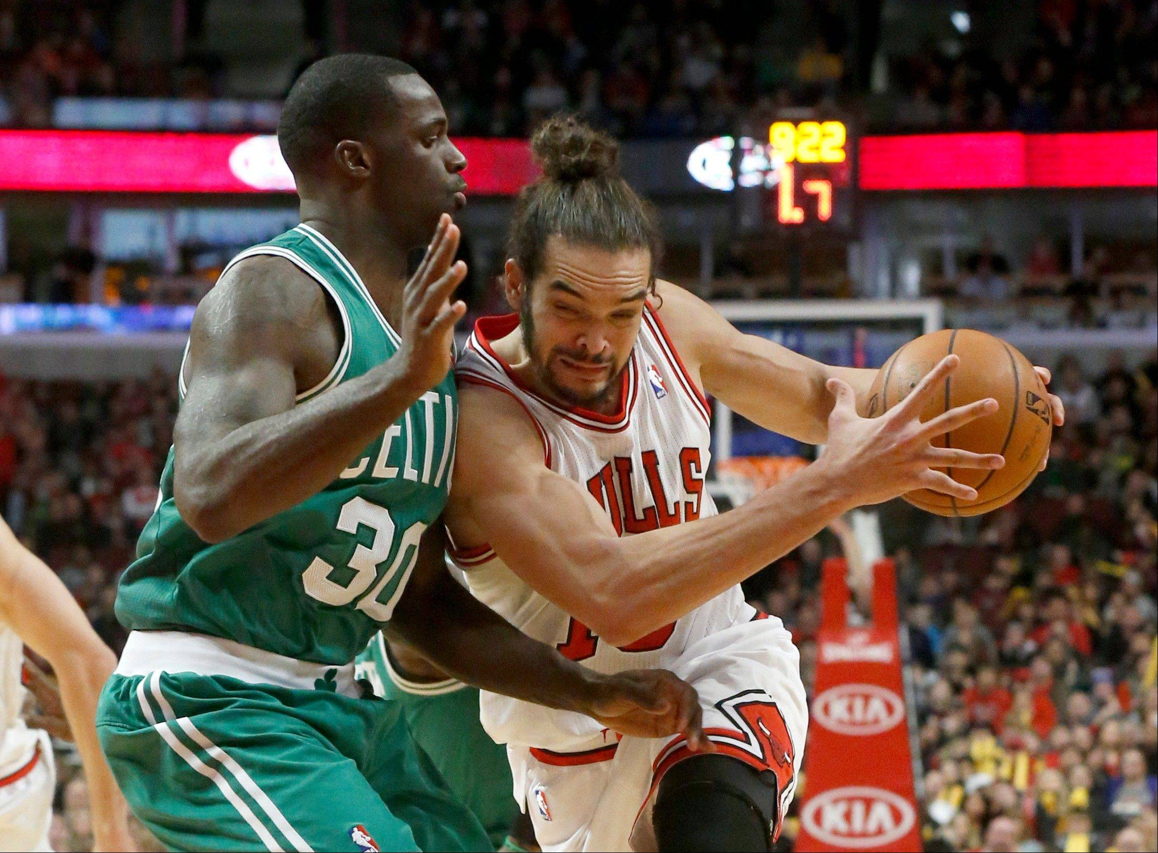 Bulls center Joakim Noah drives against Celtics forward Brandon Bass during the second half Thursday night. Noah finished 1 assist short of a triple-double.