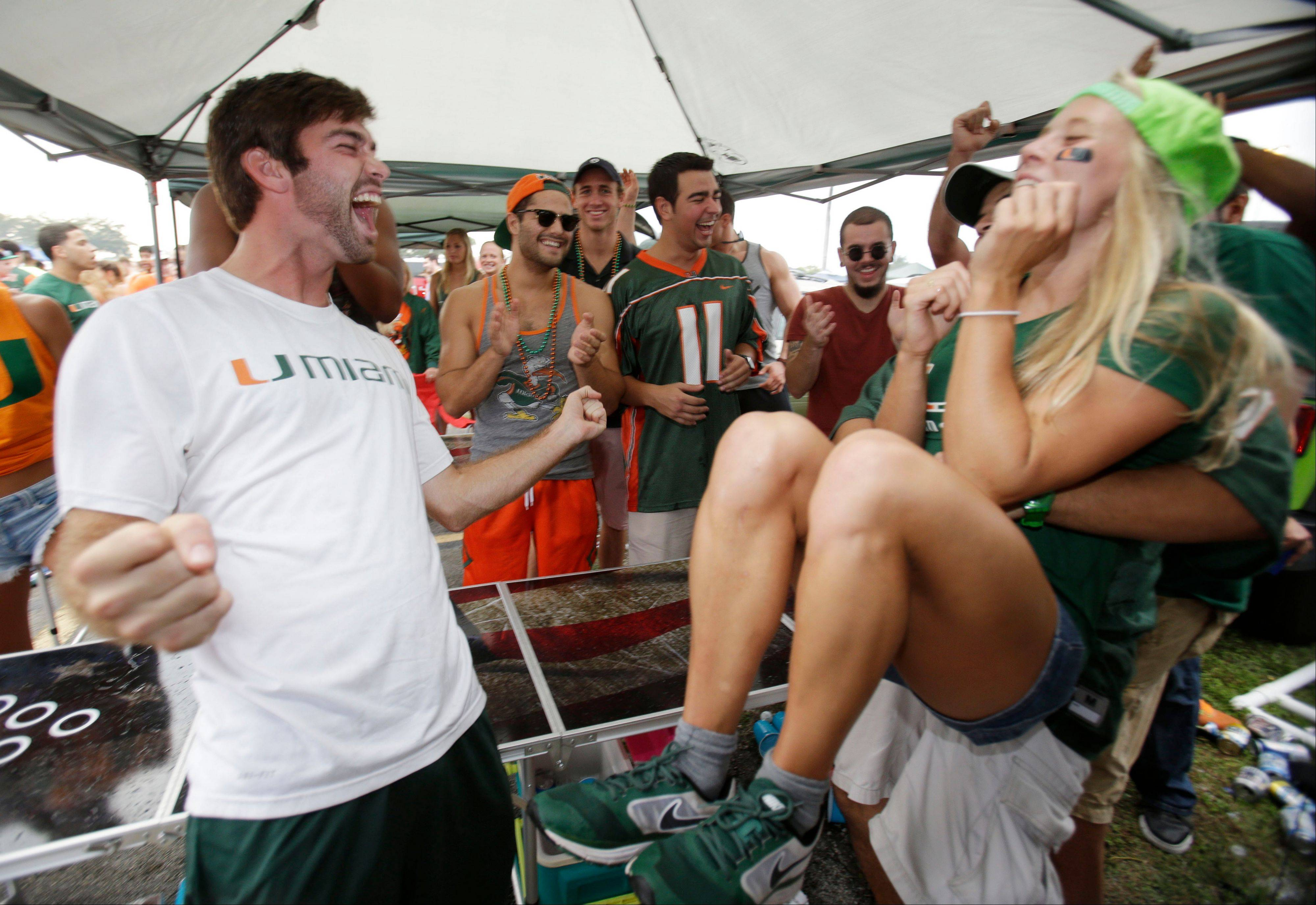 Jack Murphy, left, 20, celebrates after wining a game of pong while tailgating before the start of an NCAA college football game between Miami and Virginia Tech, in Miami Gardens, Fla. It may be the hottest tailgate party at the University of Miami's homecoming game, but the 100-yard stretch of free pizza and party tents set up by Generation Opportunity, a national conservative organization, is also a carefully crafted strategy aimed at getting students to opt out of President Barack Obama's controversial new health law.