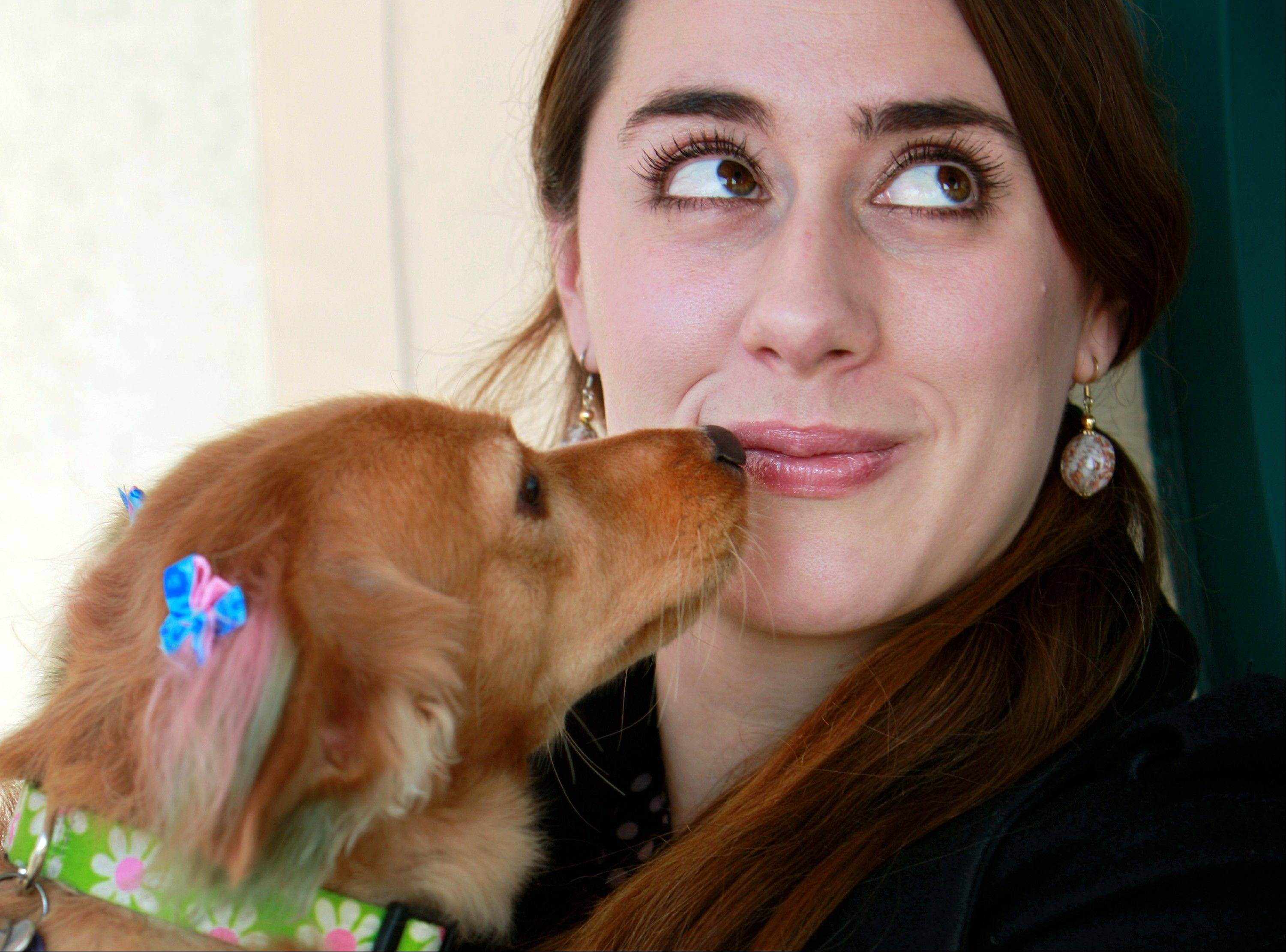 Sasha Sinnott holds her dog, a 2-year-old dachshund mix, Sugarplum, after a chalking at the PetSmart in Culver City, Calif. Sugarplum went into the salon as a reddish-blonde dachshund mix and came out with pink and green ears, a rainbow tail and a bow in her fur.