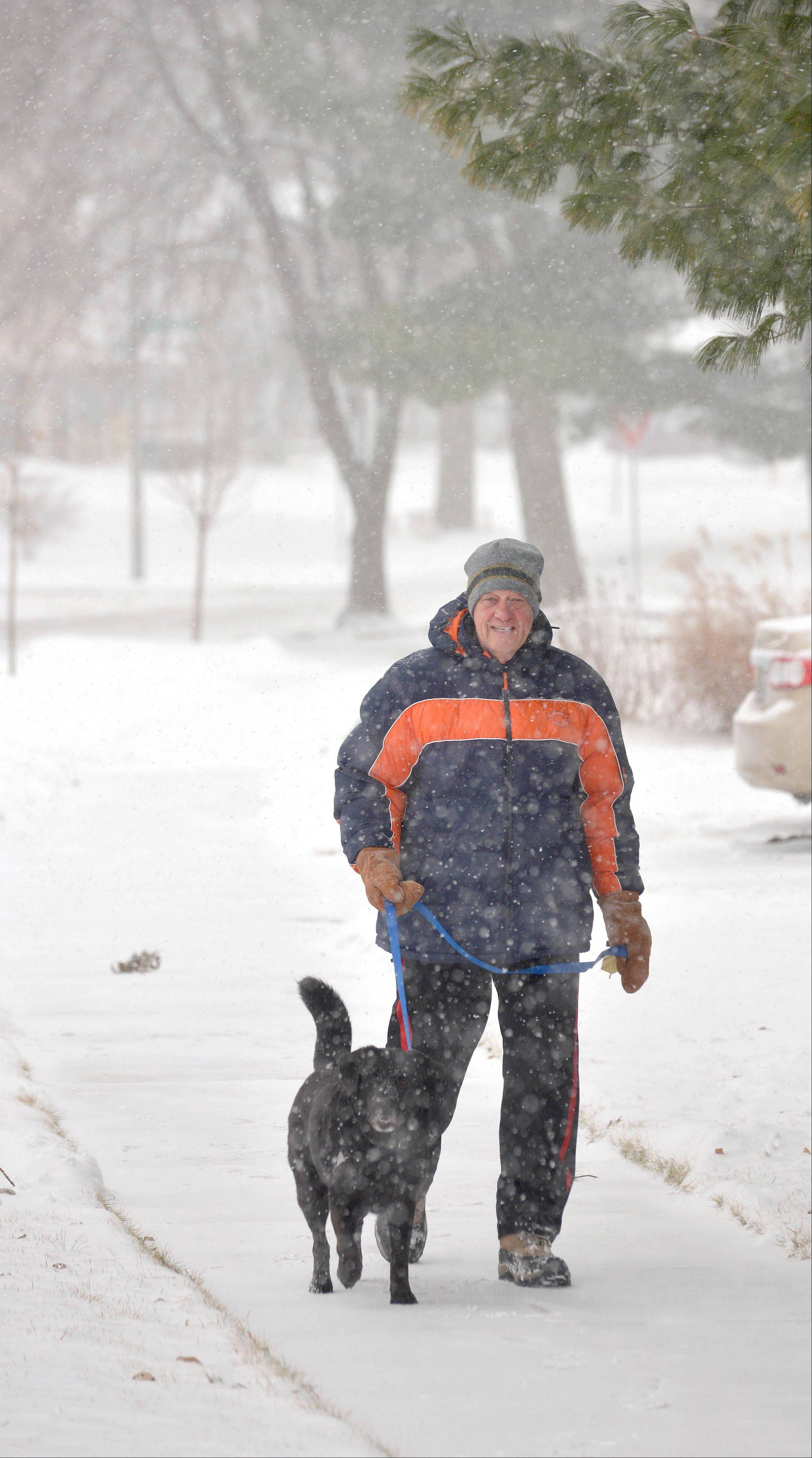 "Larry Loehr and his dog, Zoe, walk in Naperville late Wednesday morning. Loehr, who moved here from Delaware in 2007, said he loves ""the Chicago-Naperville winters and all the snow."""