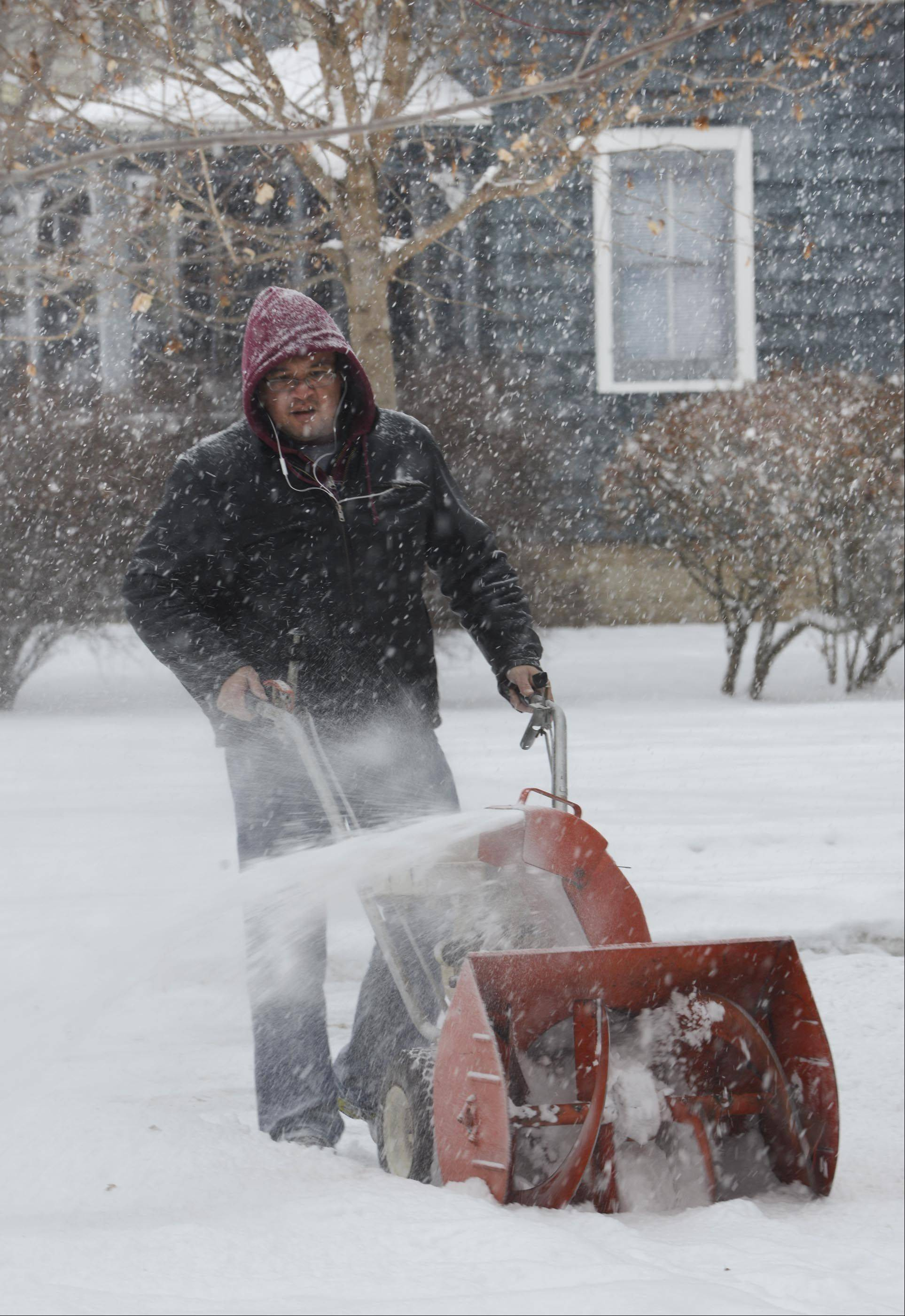 Butch Olanosa uses his old snowblower Wednesday to clear the accumulation on his sidewalk in front of his Jefferson Street home in Batavia.
