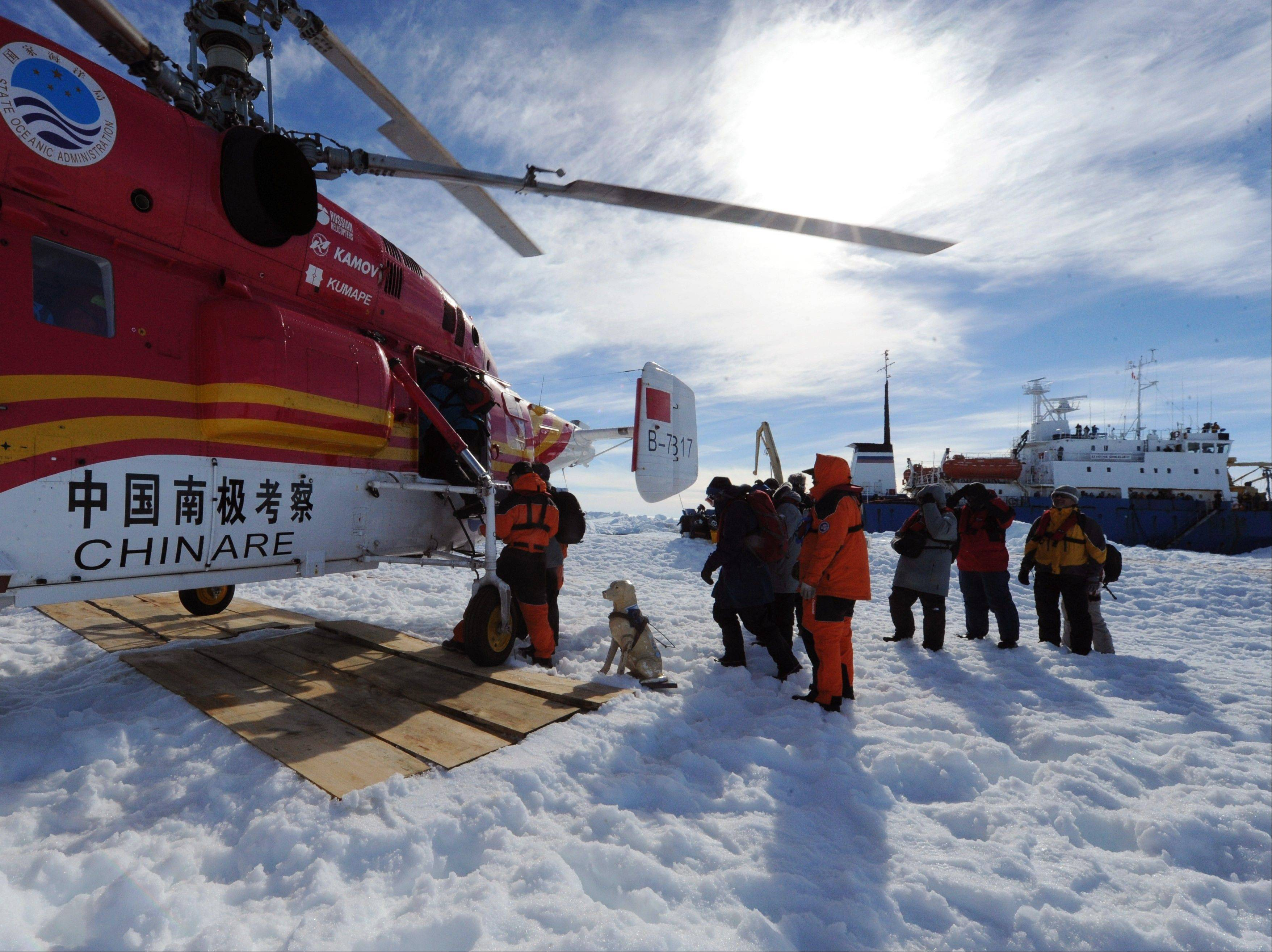 Passengers from the trapped Russian vessel MV Akademik Shokalskiy, seen at right, prepare to board a Chinese helicopter in the Antarctic Thursday. All 52 passengers from the research ship that has been trapped in Antarctic ice were airlifted to safety after weather conditions finally cleared enough for the operation.