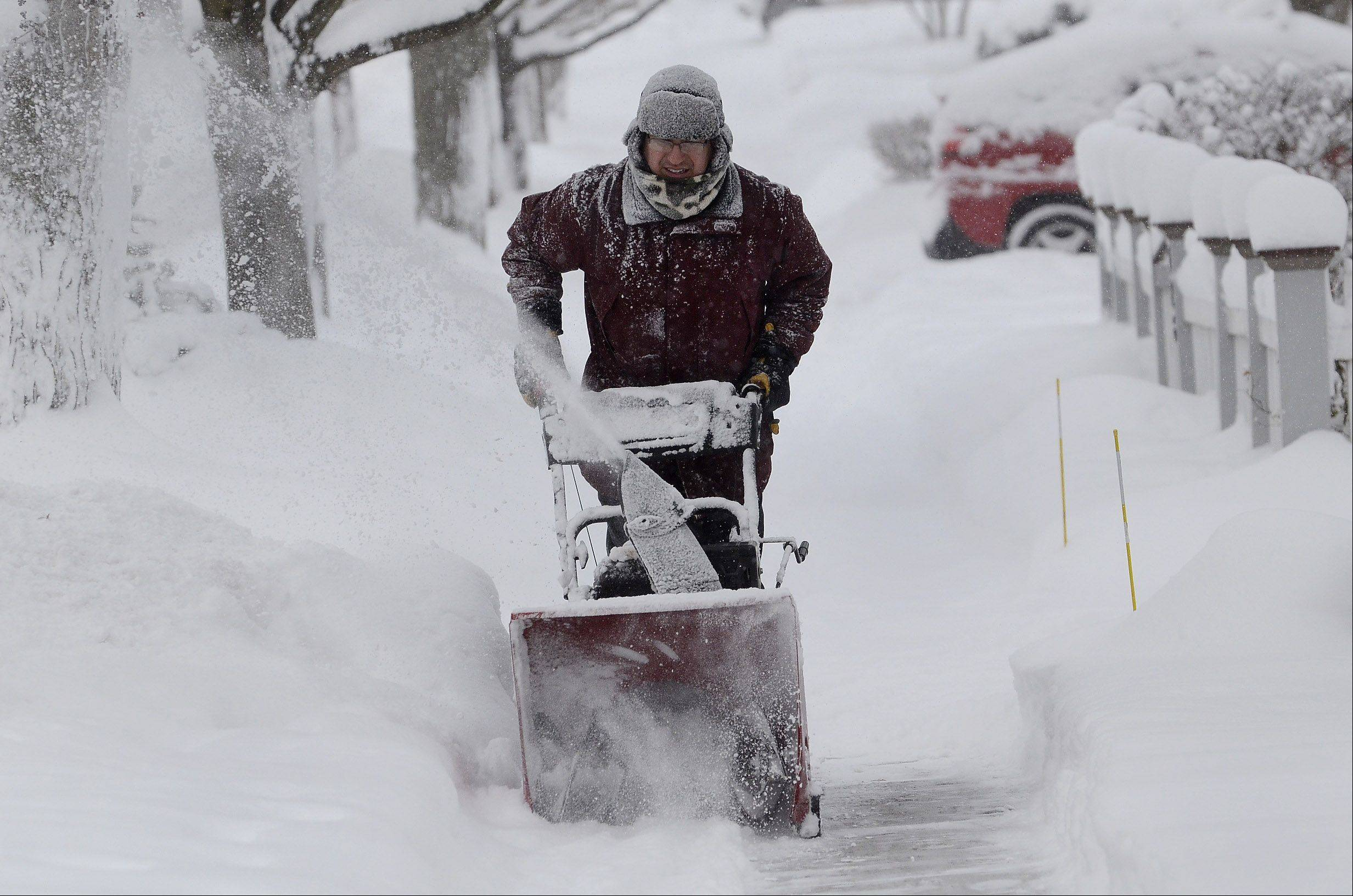 Kevin Pokorny of West Lake Street in downtown Barrington works on clearing snow from neighbors' driveways and sidewalksThursday morning.