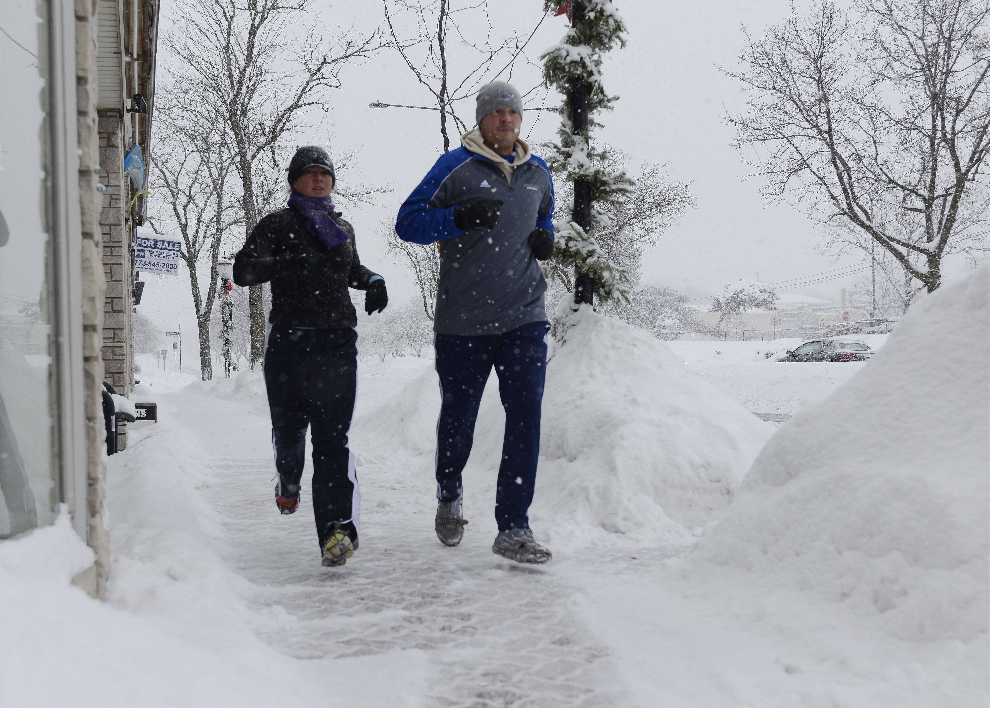 Jessica Tomasiewicz of Mount Prospect and her husband Kevin jog in the snow alongside Prospect Avenue in Mount Prospect Thursday.