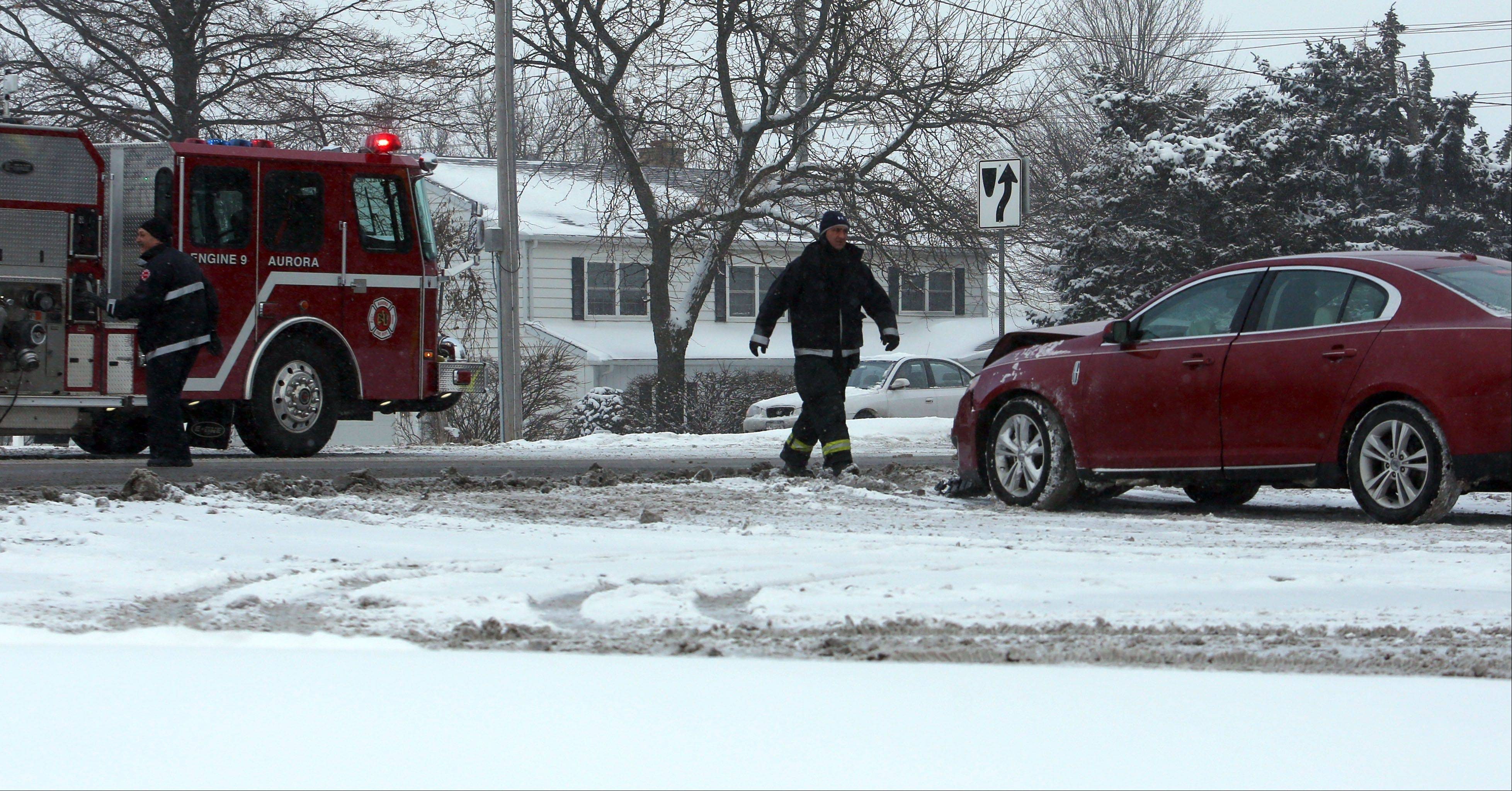 Aurora firefighters move a car out of traffic after a car accident on northbound Eola Road in Aurora on Thursday.