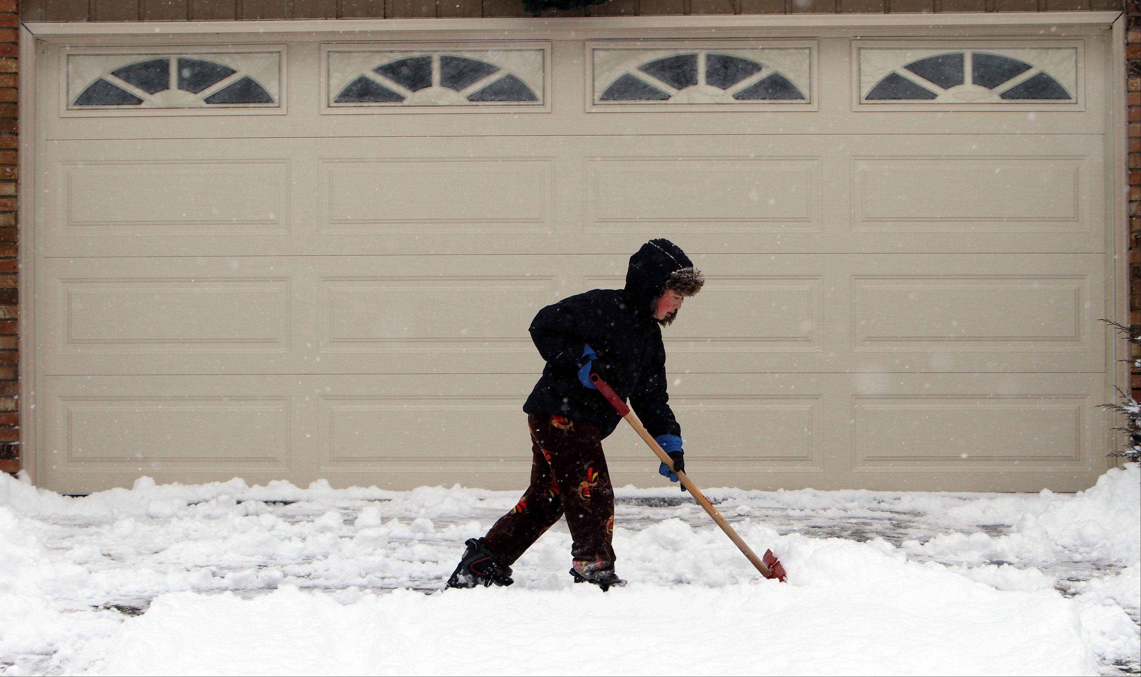 12-year-old Dylan McCauley of Libertyville shovels his driveway Thursday morning after a snowstorm dumped almost a foot of snow on the area.