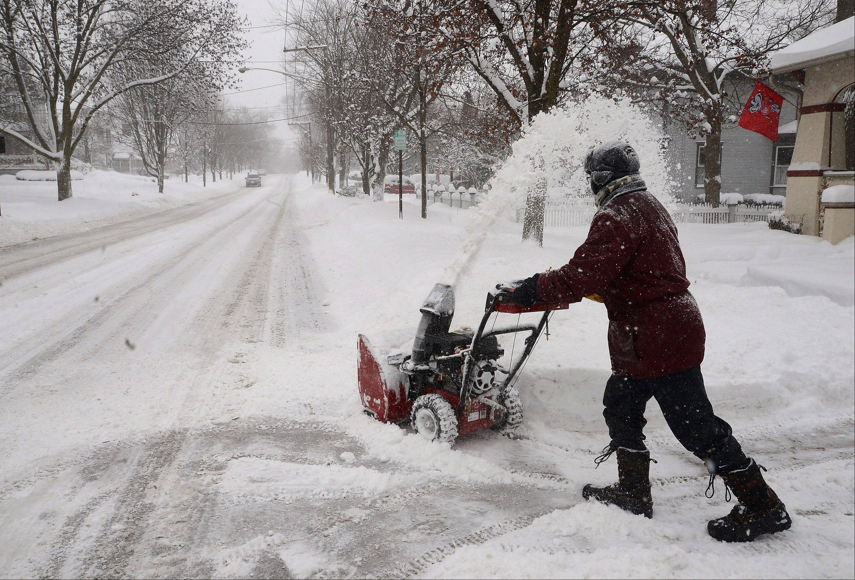 Kevin Pokorny of West Lake Street in downtown Barrington works clearing snow from neighbors' driveways and sidewalks Thursday morning, as Barrington woke up to 10 plus inches of snow overnight.