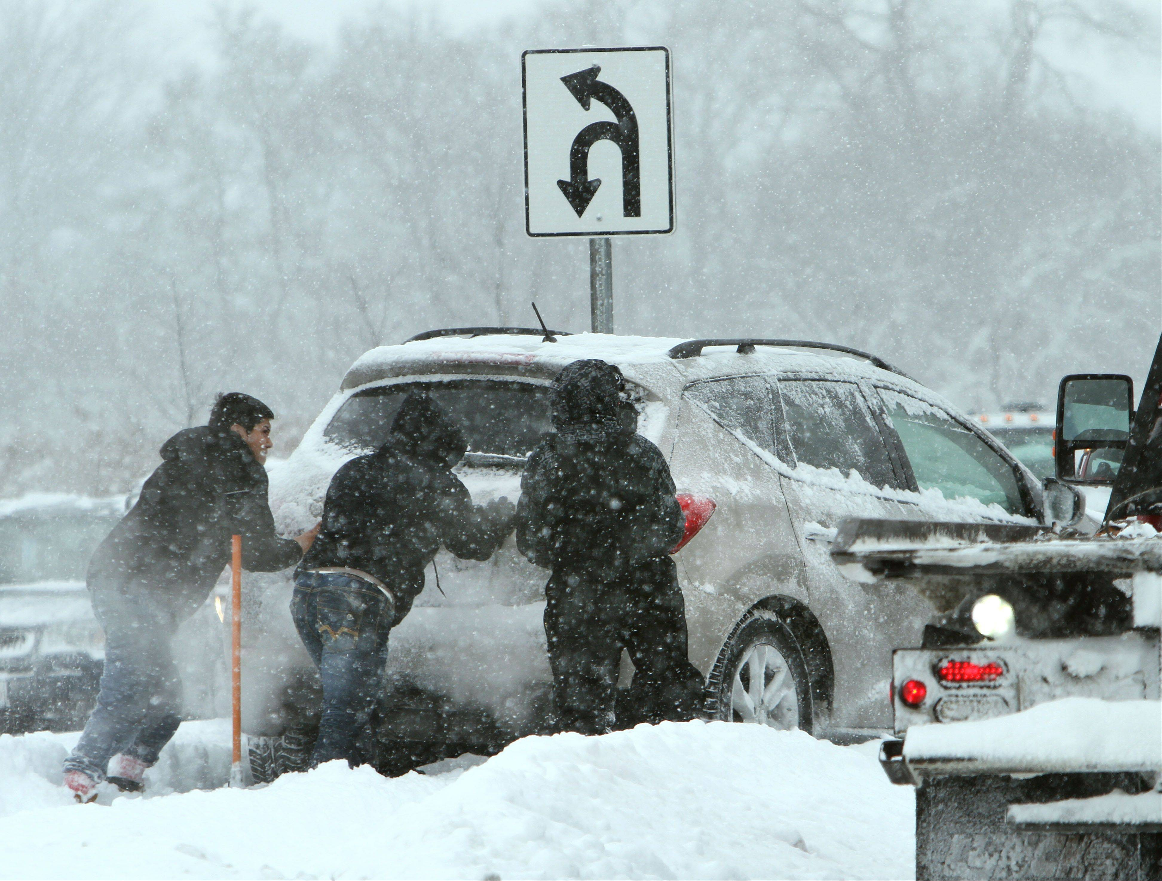 Good samaritans help a woman who lost control and ended up on the median on Route 45 and Center Street in Grayslake Thursday. Heavy snow over the last couple of days has made the roads dangerous.