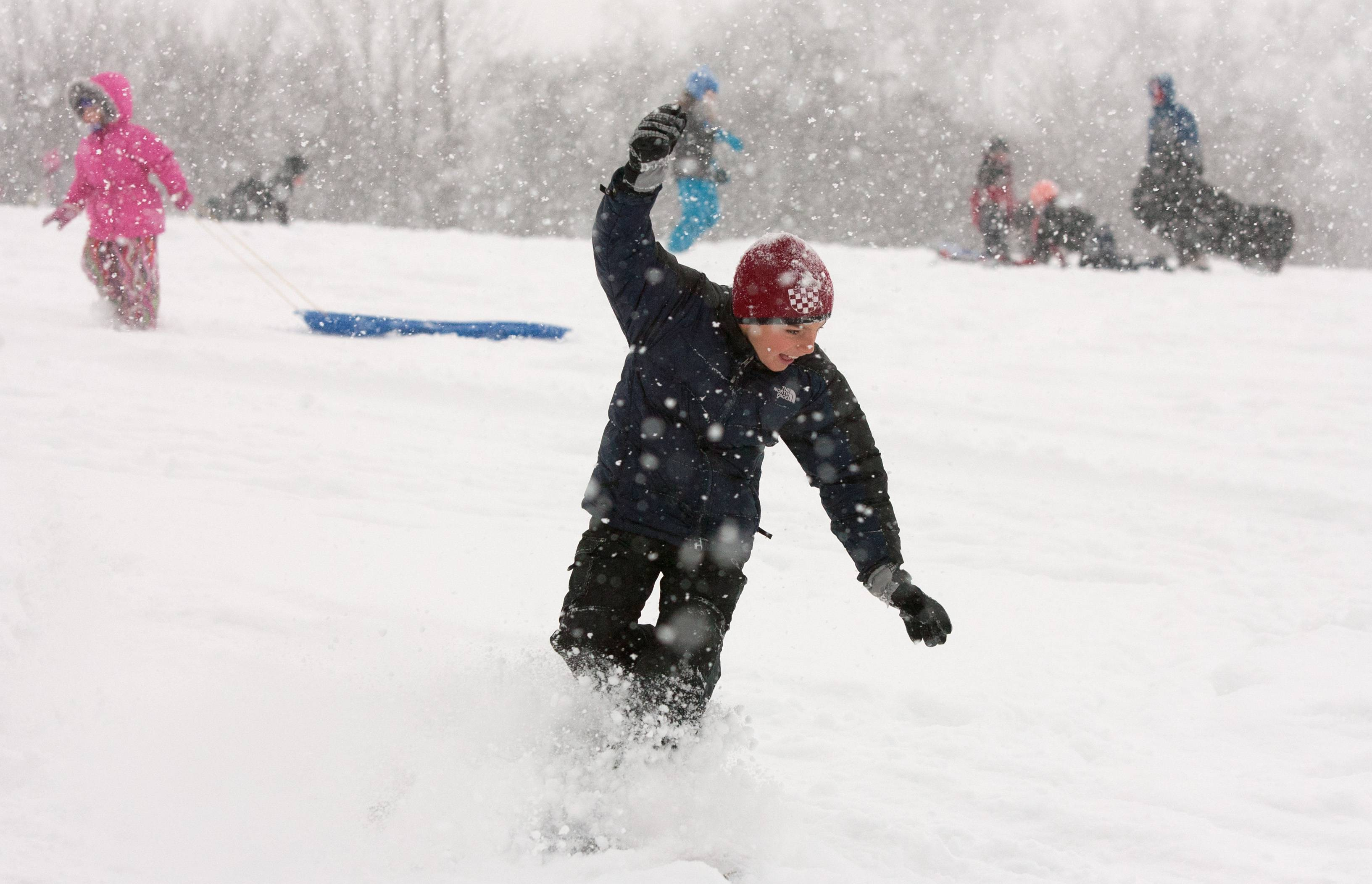 Matt Peso of Western Springs enjoys snow boarding down a hill next to the Oak Brook Public Library.