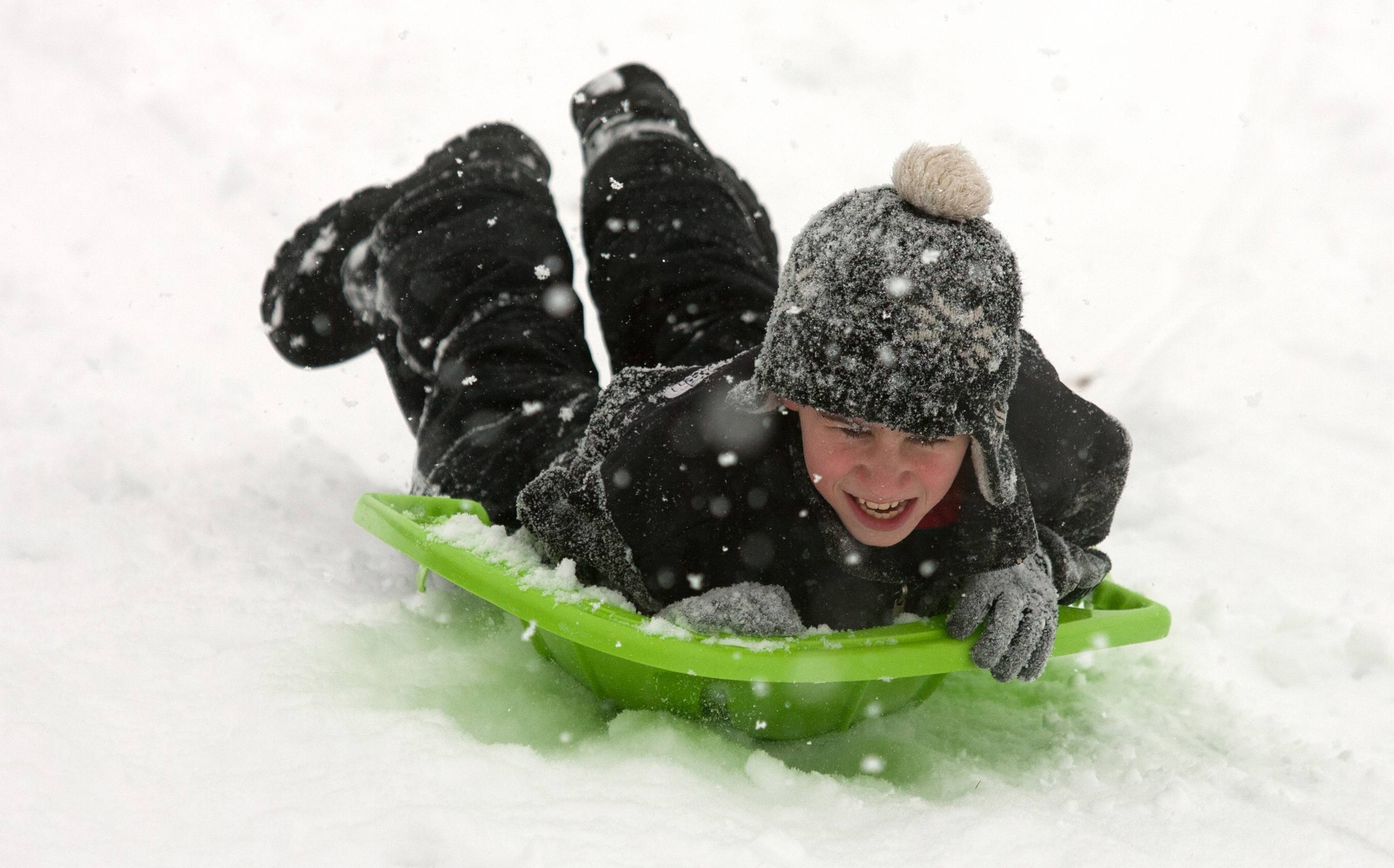 Kevin Hogan of Western Springs enjoys sledding down a hill next to the Oak Brook Public Library.