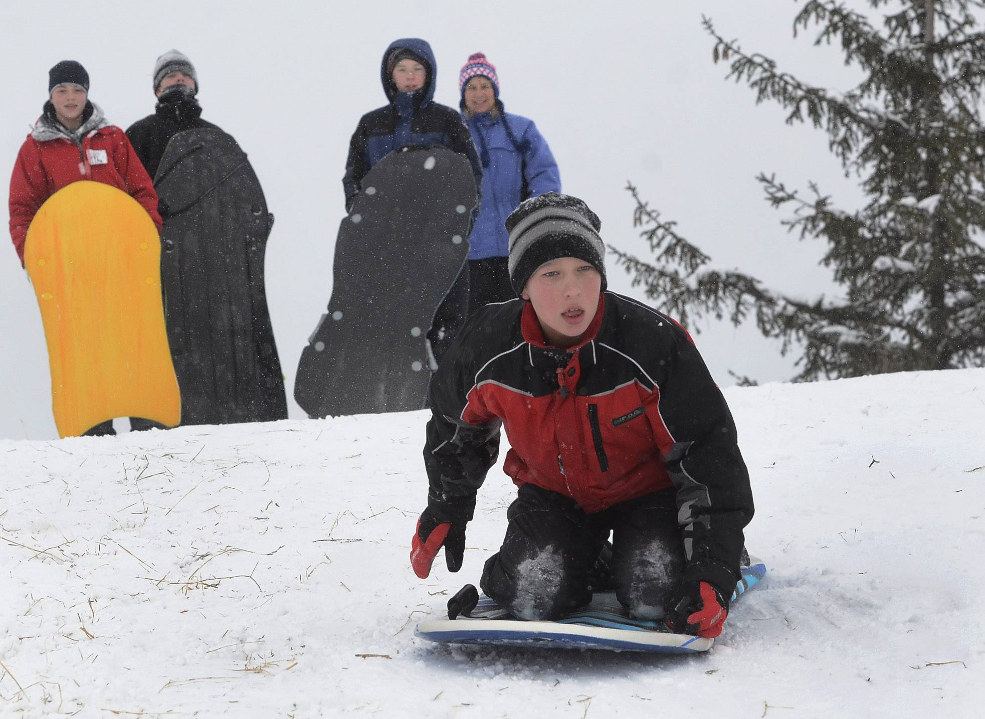 With his buddies urging him on, Timmy O'Reilly of Palatine heads down the hill on his sled at Reimer Reservoir in Palatine.