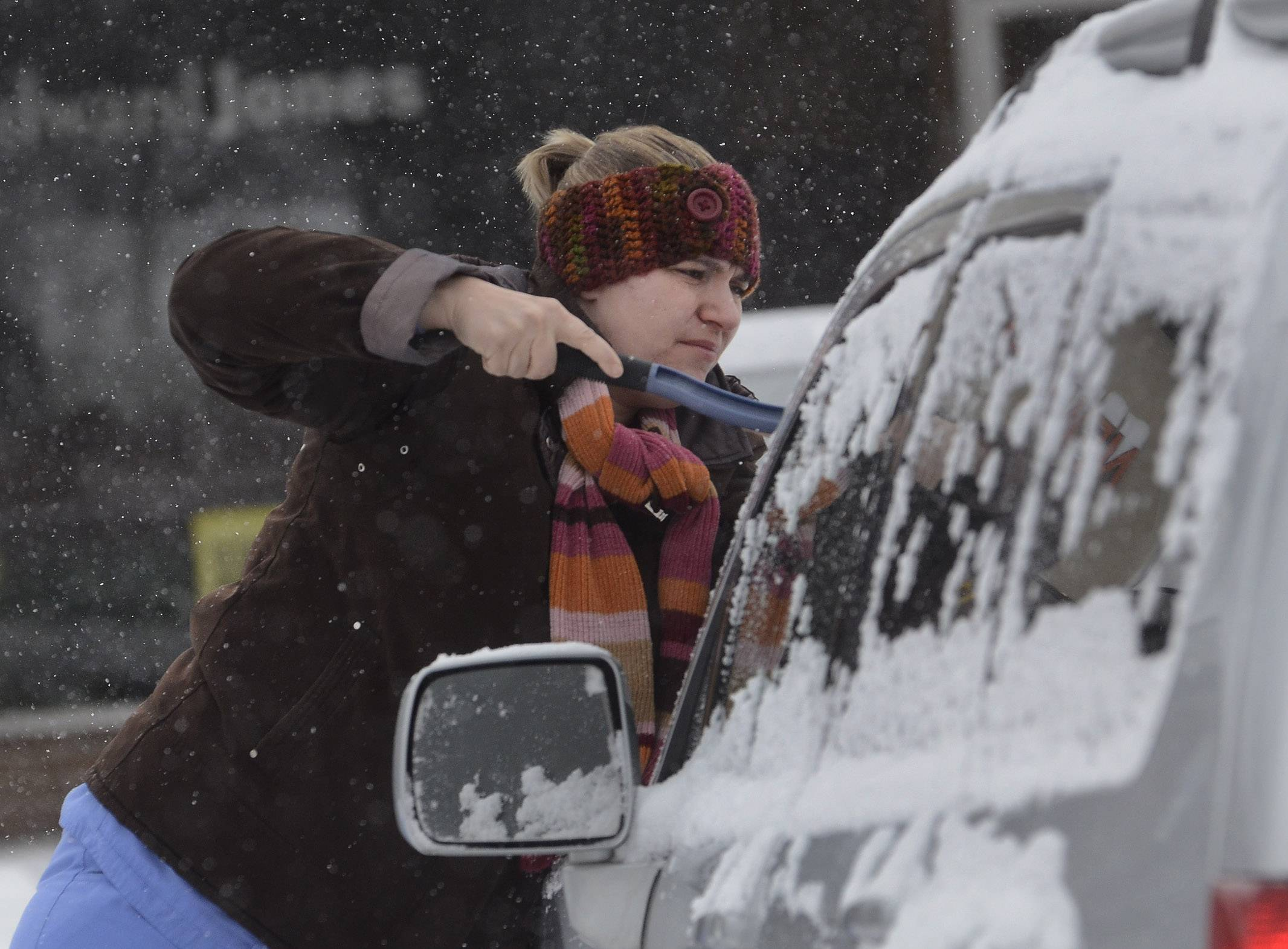 Jill Kaergard of Schaumburg scrapes off the snow from her vehicle on a lunch break from her Dentist's office job at Campbell and Wilke in Arlington Heights.