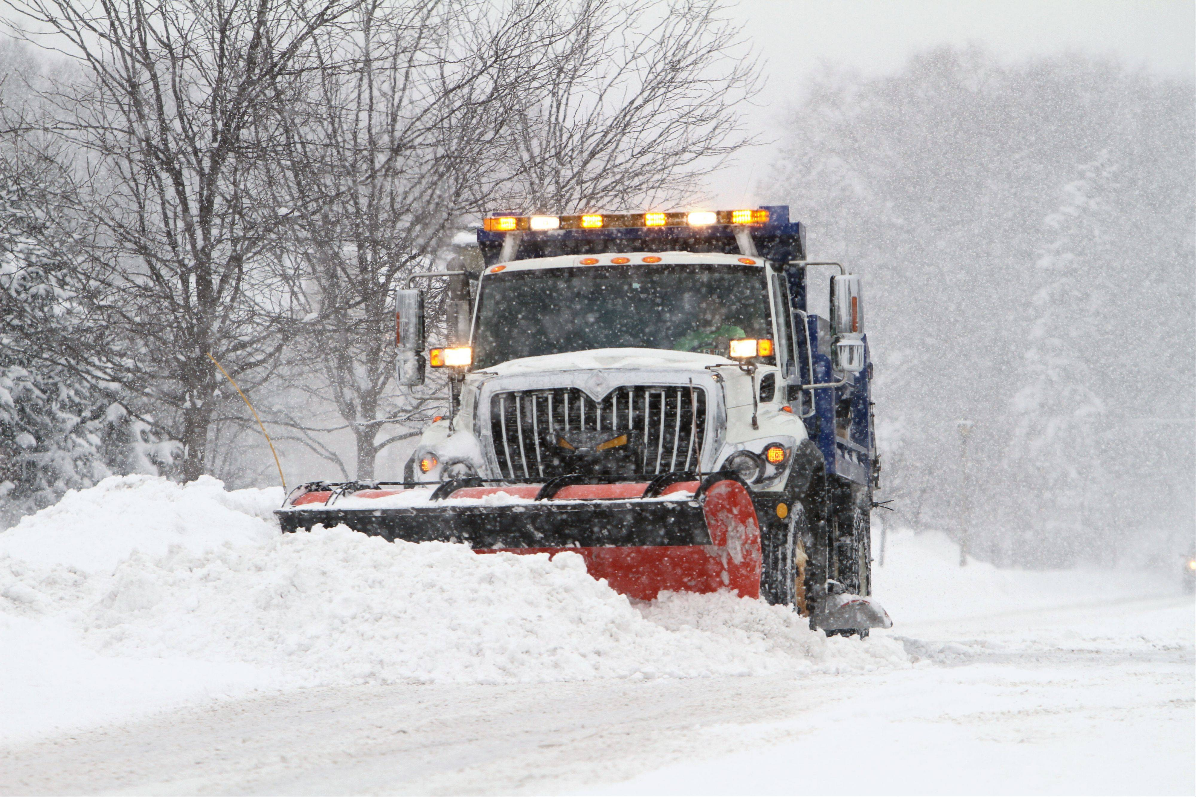 A snowplow makes its way down Garfield Avenue in Libertyville Thursday morning after a snowstorm dumped almost a foot of snow on the area.