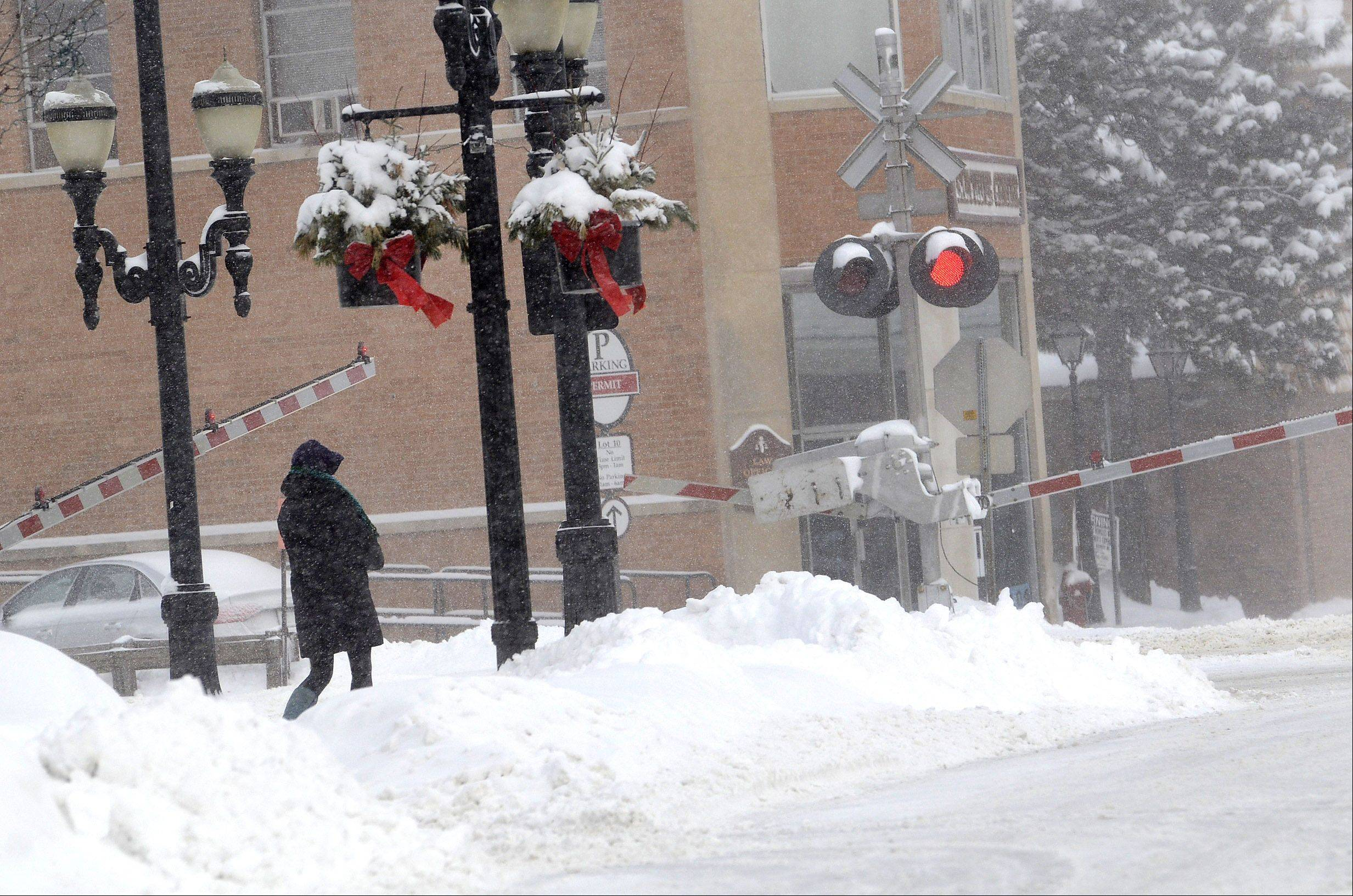 Pedestrians struggle to navigate through the snow Thursday morning in downtown Barrington.