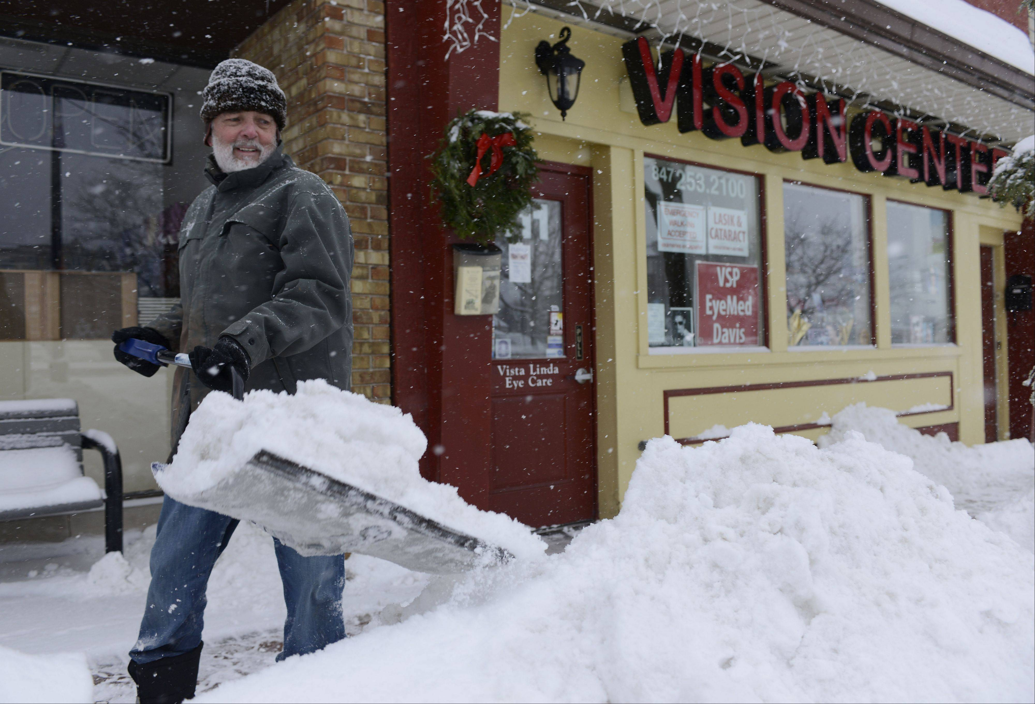 Bill Murray shovels now from the sidewalk in front of his wife's vision care center on Prospect Avenue in Mount Prospect Thursday.