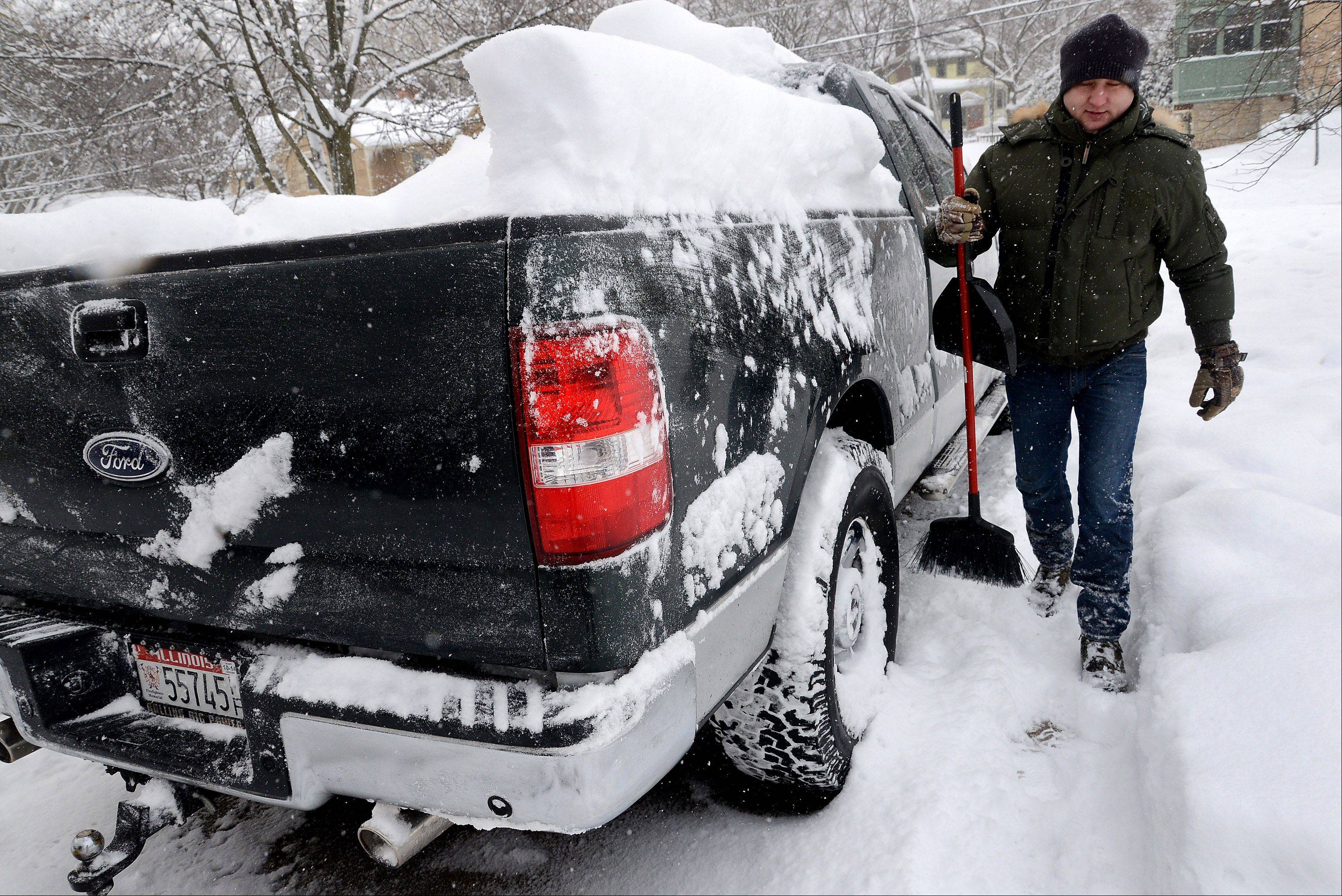 David Paluch brushes off snow from his truck in front of his home on Station Street in downtown Barrington in preparation to take his family sledding.
