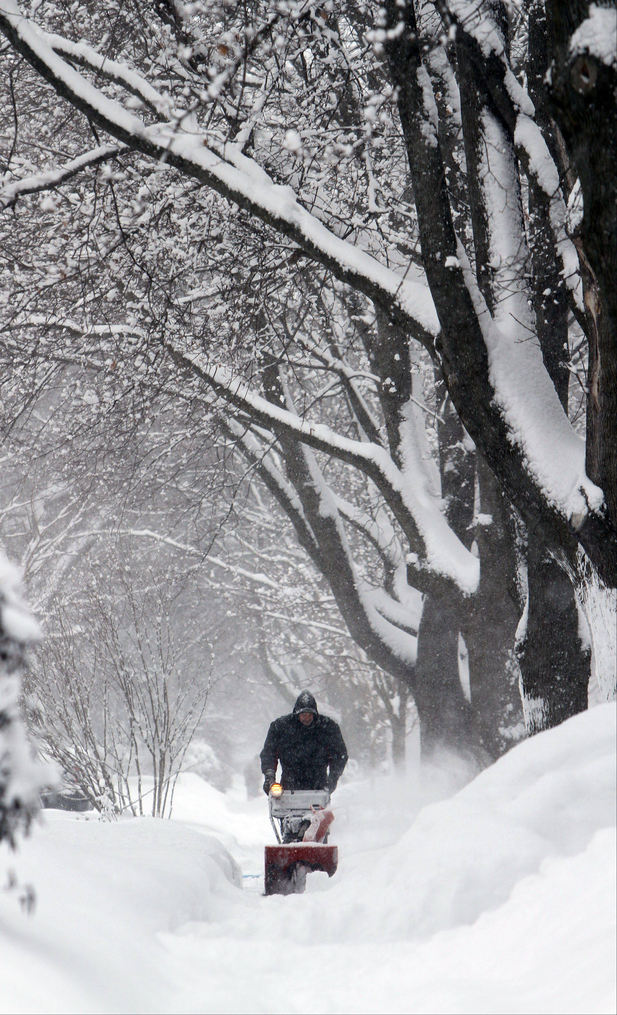 George Hoffman snow blows his sidewalk along Burdick Street in Libertyville on Thursday after a snowstorm dumped almost a foot of snow on the area.