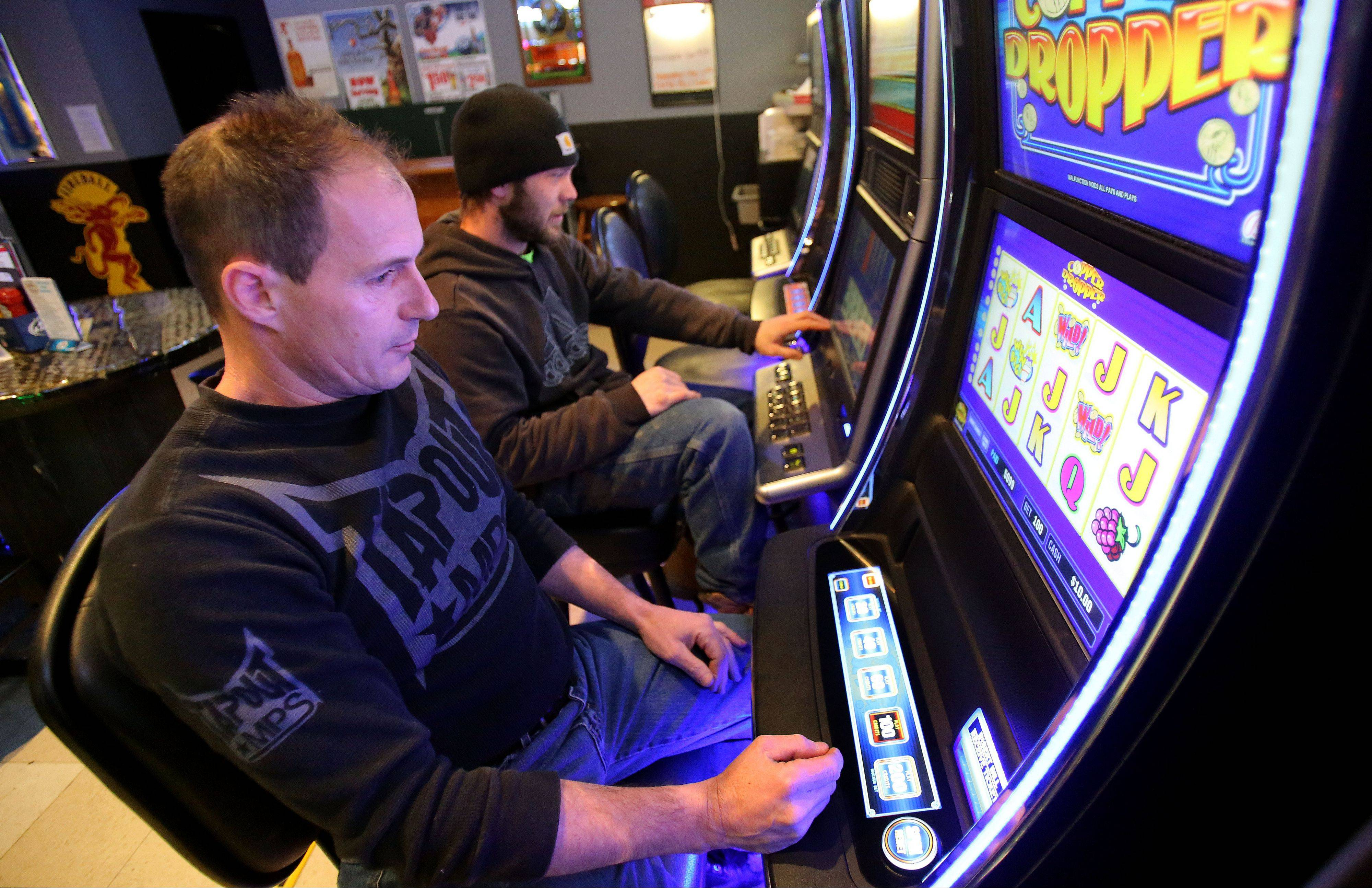 Mike Mitlevic, left, of Fox Lake and Rob Jones of Long Lake, play video gambling games at J's Sports Bar in Fox Lake. Village officials said the first year of video gambling generated more than $93,000 for the village.