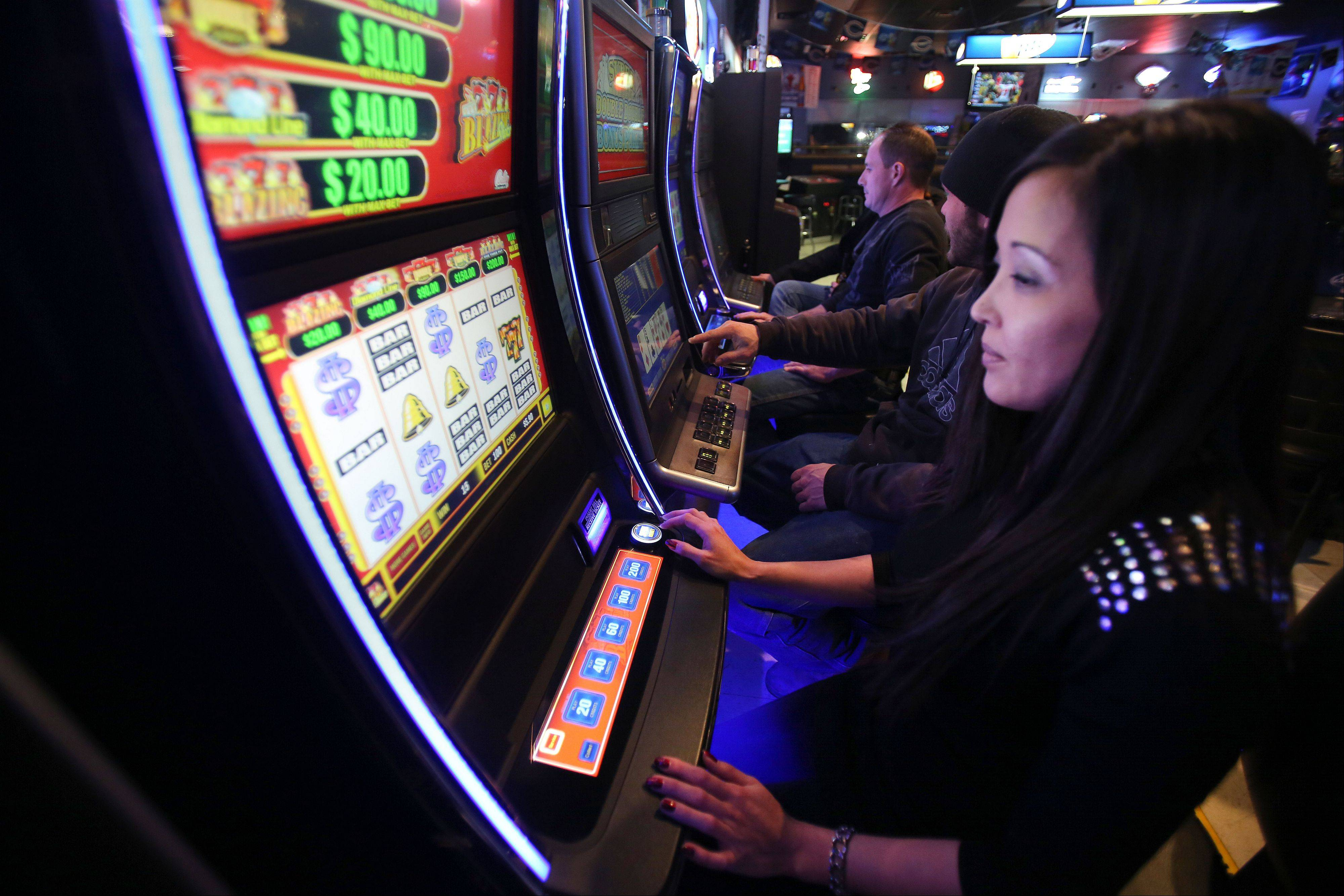 Kim Kitahata, of Lakemoor, plays a video gambling game at J's Sports Bar in Fox Lake. Village officials said they hit the jackpot by collecting more than $93,000 in revenue in the first year video gambling machines operated.