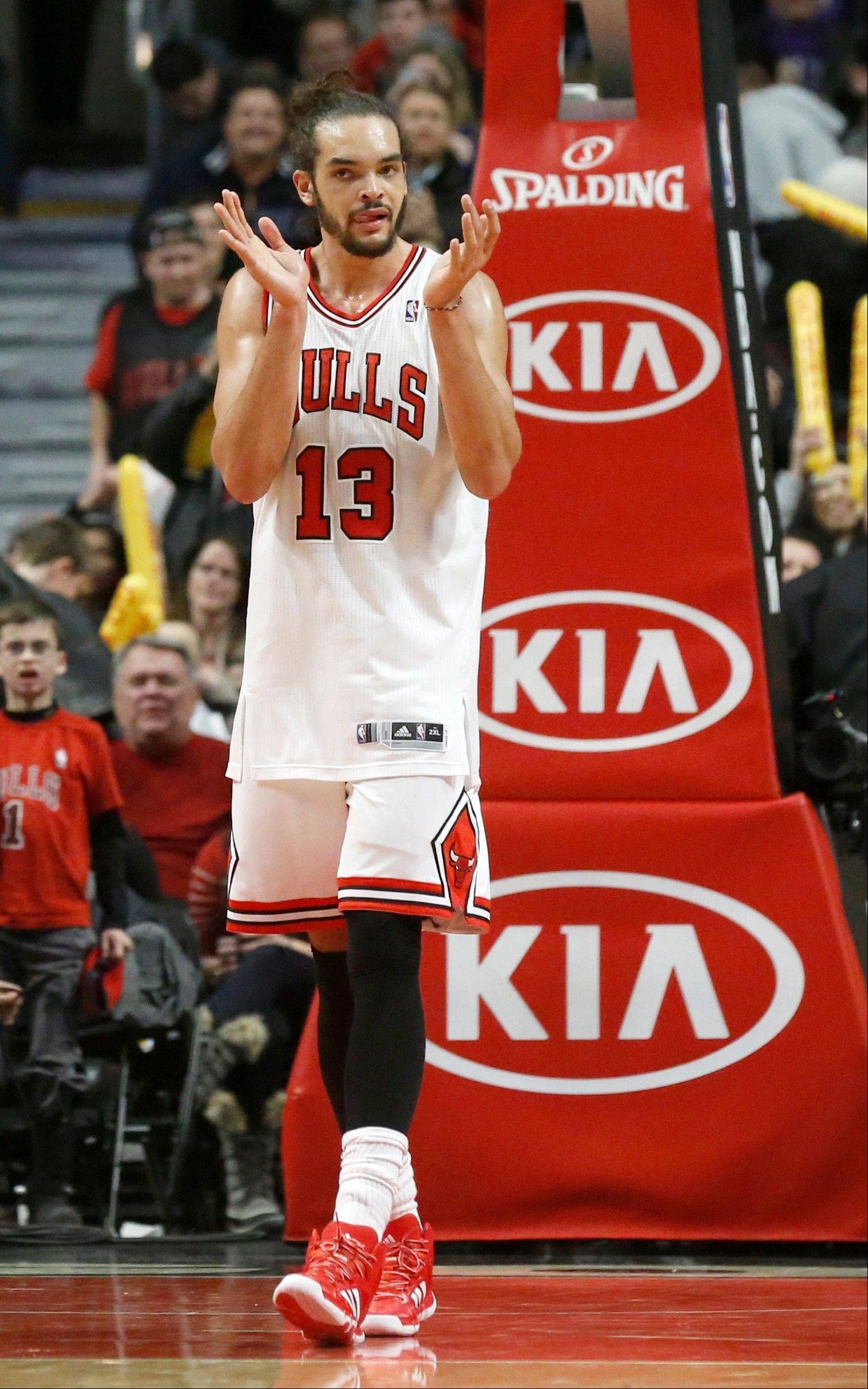 Chicago Bulls center Joakim Noah applauds his teammates during the second half of an NBA basketball game against the Boston Celtics, Thursday, Jan. 2, 2014, in Chicago. The Bulls won 94-82.