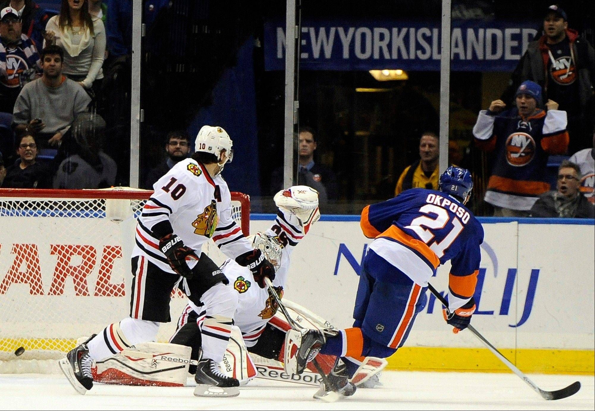 The Islanders' Kyle Okposo shoots the puck past Blackhawks goalie Corey Crawford as Patrick Sharp watches in overtime Thursday night. It was Crawford's first start since missing 10 games with a groin injury.