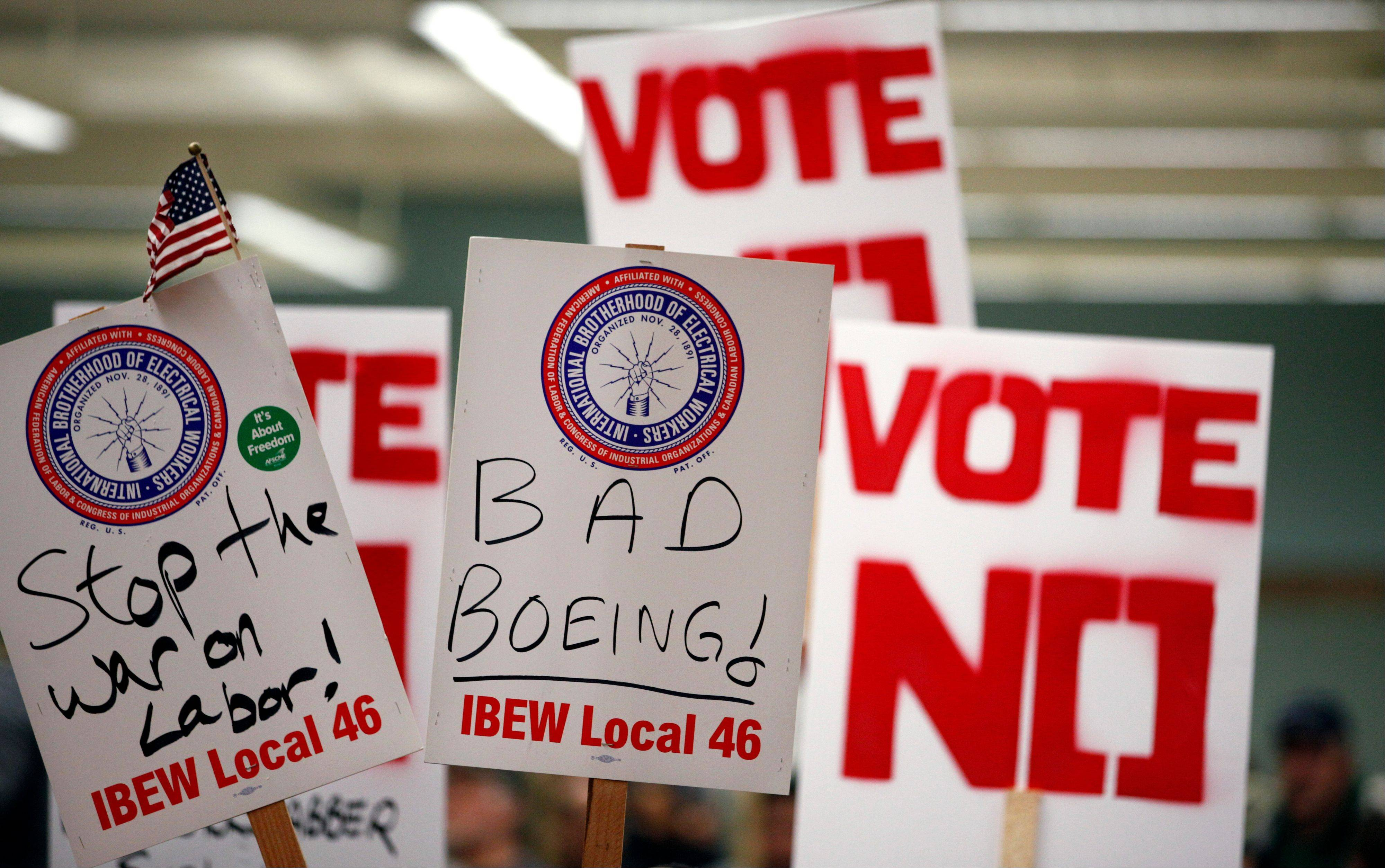Signs urging a no vote are held up at a rally asking members to vote against a proposed contract Thursdayin Seattle.