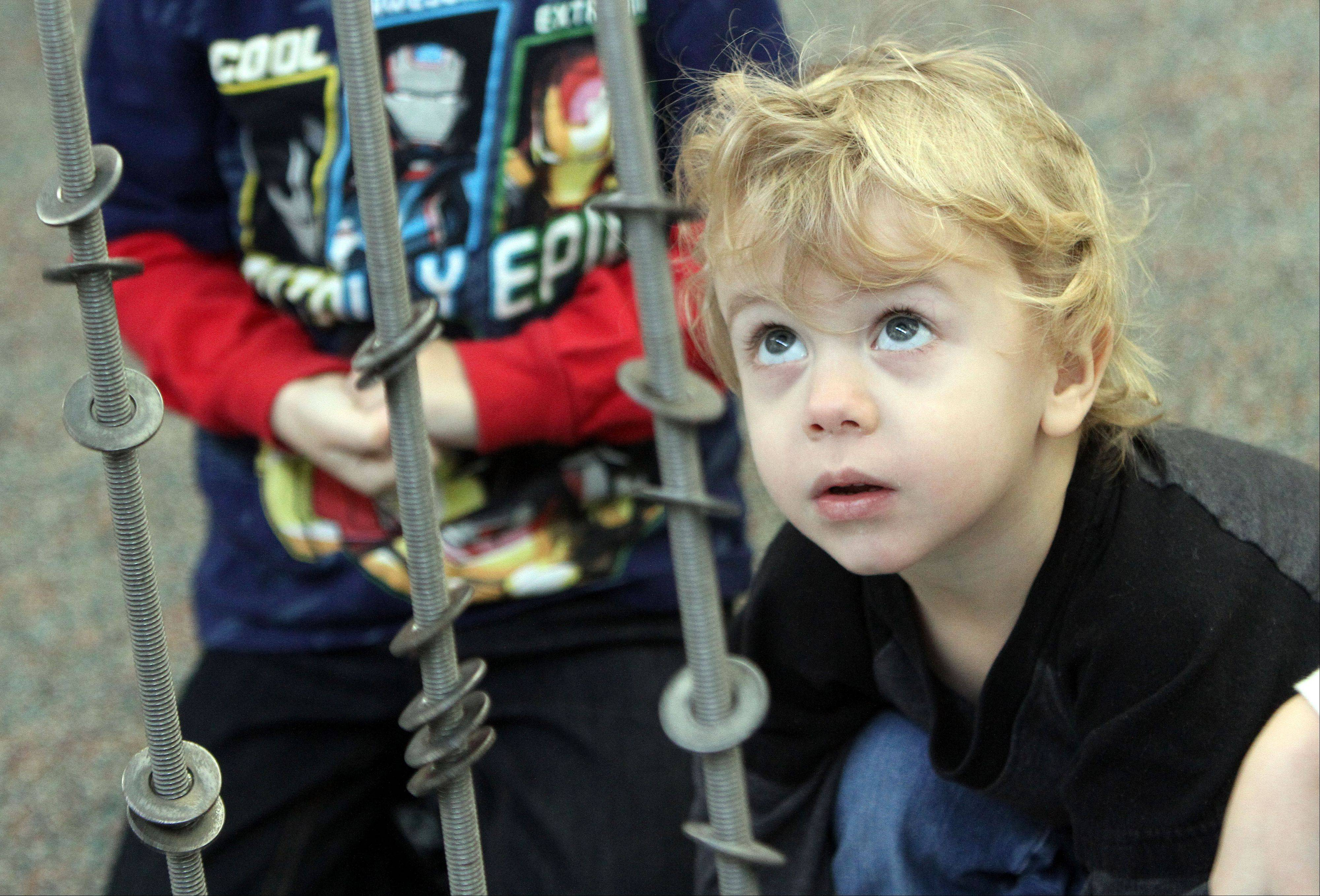 Shane Jones, 2, of Round Lake Beach, watches washers fall down a metal pipe Friday during the Busy Brains Children's Museum program at Lake Villa District Library in Lake Villa.