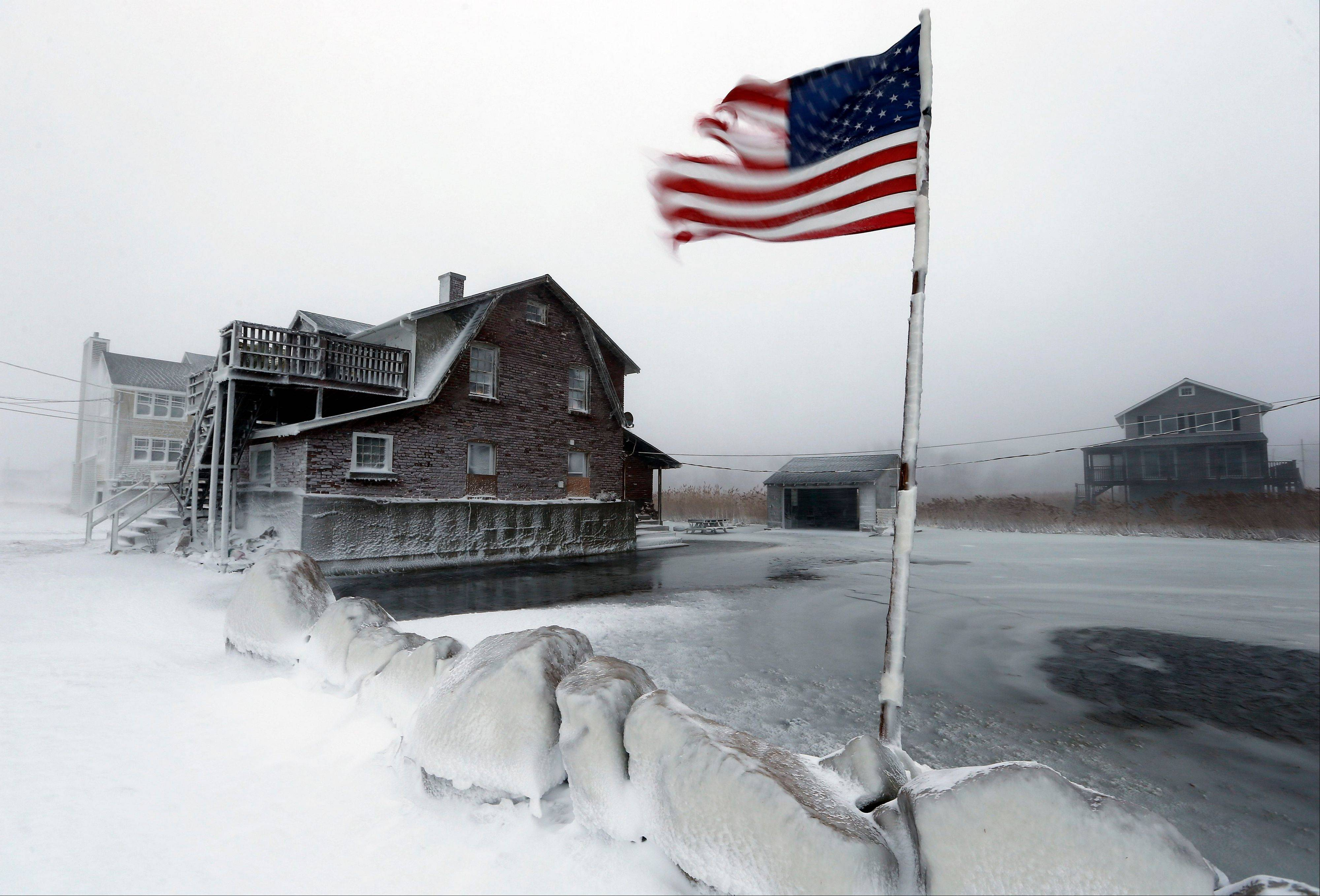 A tattered flag flies by a flooded yard along the shore in Scituate, Mass., Friday, Jan. 3, 2014. A blustering winter storm that dropped nearly 2 feet of snow just north of Boston, shut down major highways in New York and Pennsylvania and forced U.S. airlines to cancel thousands of flights nationwide menaced the Northeast on Friday with howling winds and frigid temperatures.