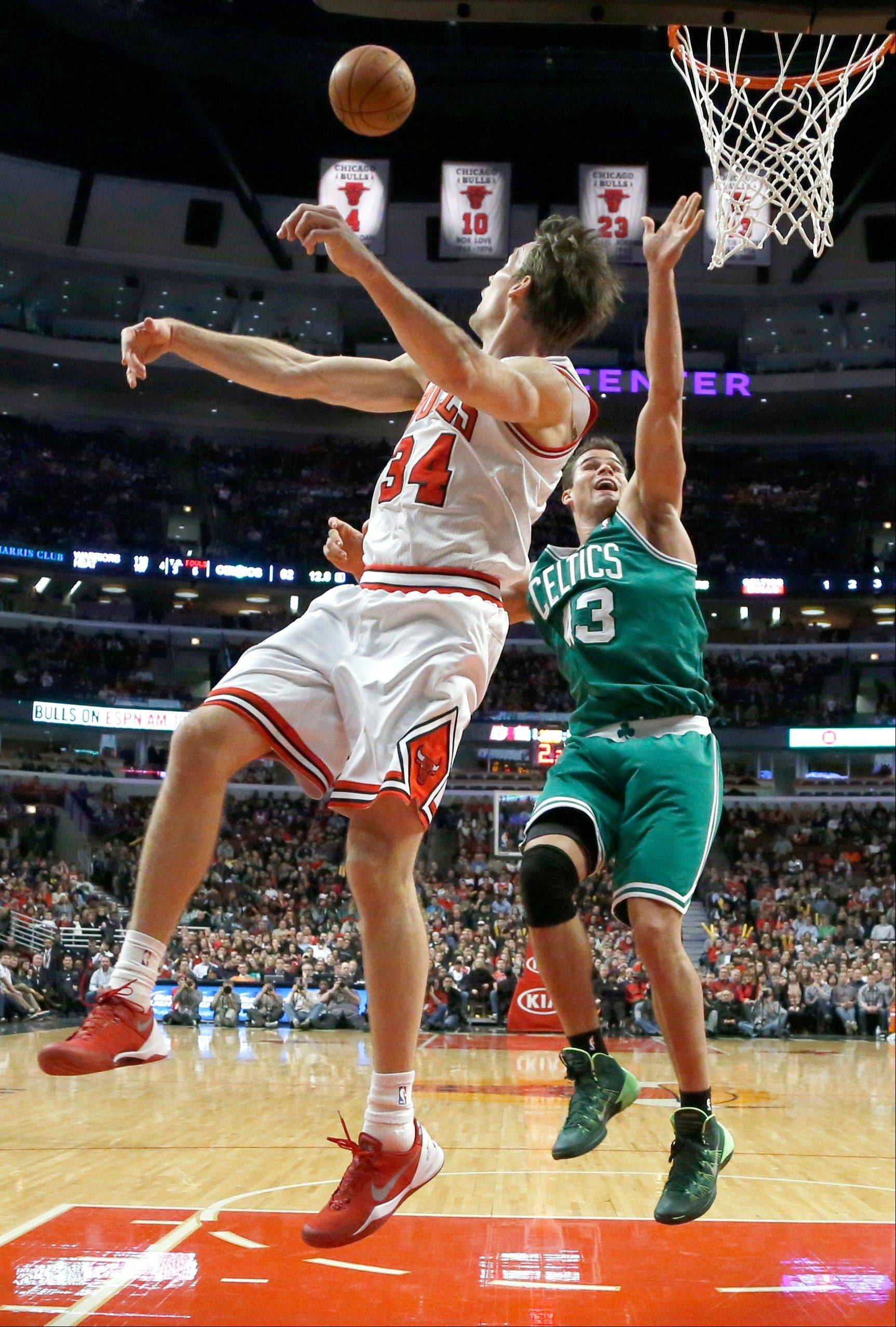 Chicago Bulls forward Mike Dunleavy (34) blocks the shot of Boston Celtics forward Kris Humphries (43) during the second half of an NBA basketball game on Thursday, Jan. 2, 2014, in Chicago. The Bulls won 94-82. (AP Photo/Charles Rex Arbogast)