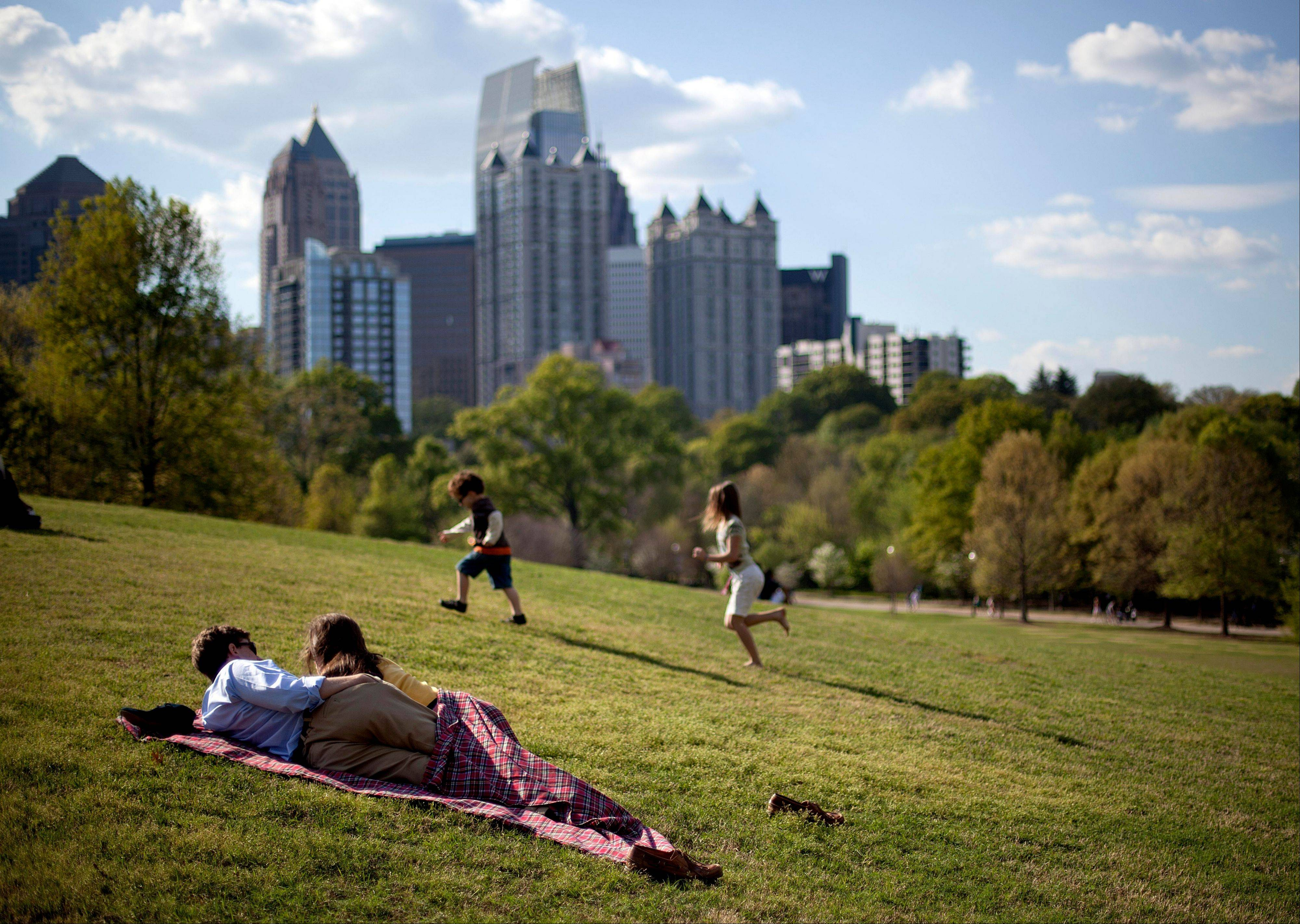 A couple enjoys a sunny afternoon against the backdrop of the Midtown skyline from Piedmont Park in Atlanta. The nearly 200-acre green space in Midtown gives Atlanta residents and visitors a tranquil setting to picnic, play games, walk their dogs and relax in the meadow or along the shores of Lake Clara Meer.
