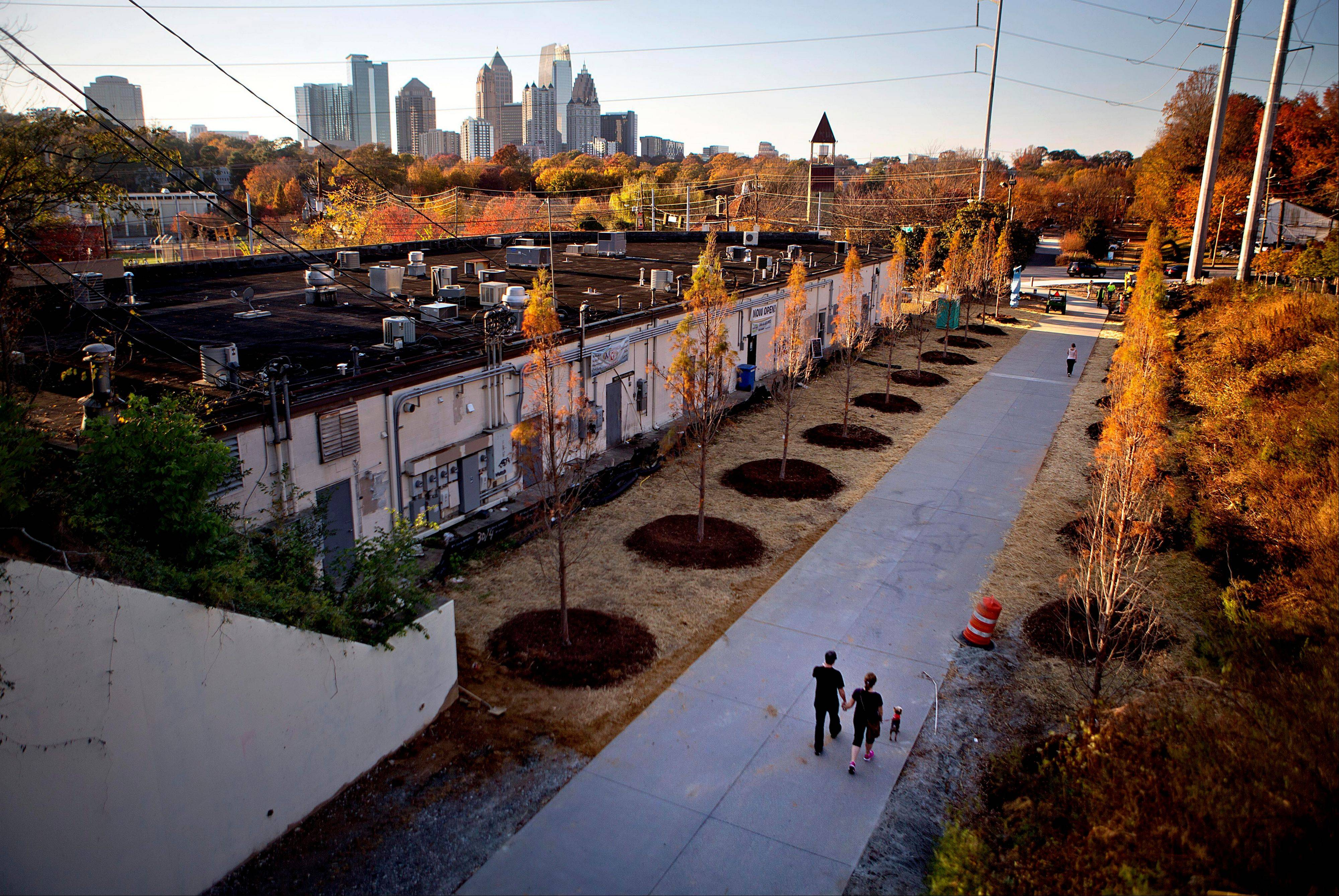 A couple walks along the Atlanta BeltLine as the midtown skyline stands in the background in Atlanta. The Atlanta BeltLine is an urban redevelopment project that aims to turn an old 22-mile railroad corridor that rings the city's in-town neighborhoods into a network of trails, parks, affordable housing and, eventually, transit.