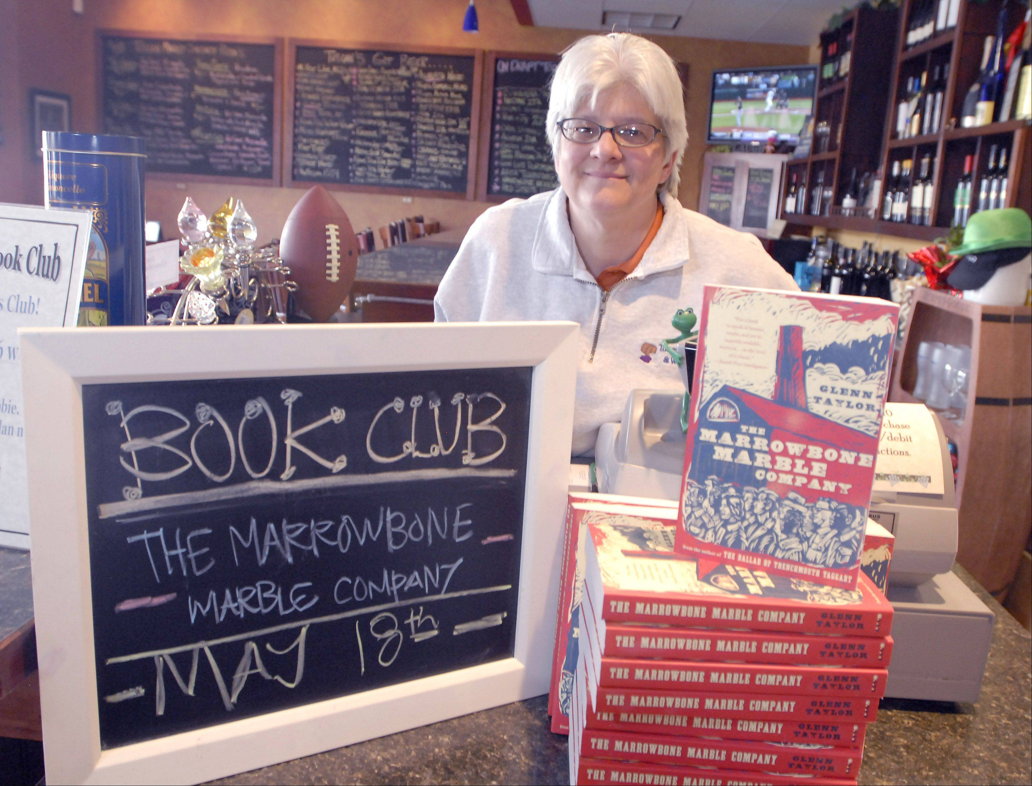 Debbie Smart shows off a book club selection at Tuscan Market in Arlington Heights.