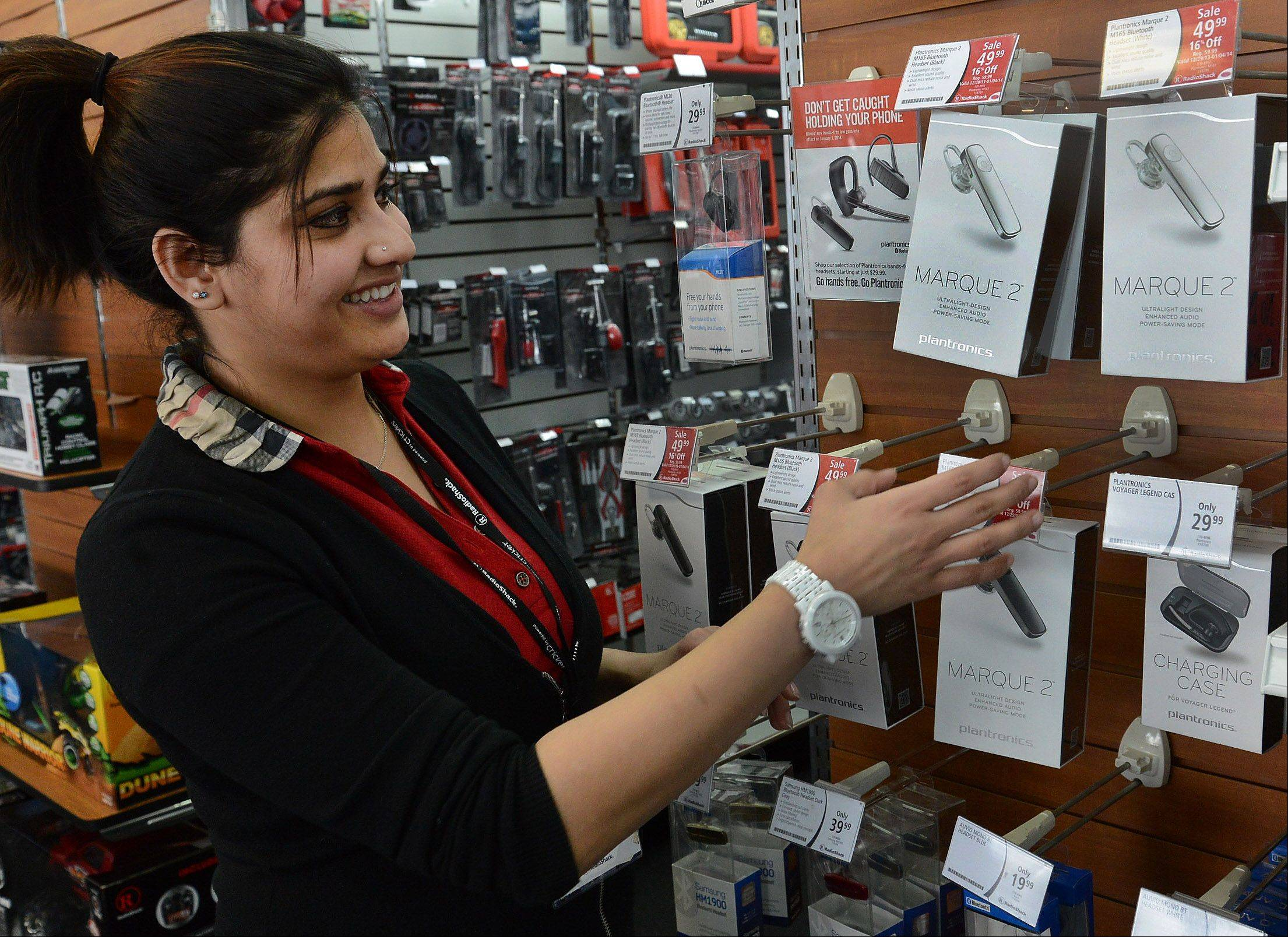 Arlington Heights Radio Shack store manager Sadaf Farooqui shows the various Bluetooth devices available at her store. Sales of Bluetooth devices have spiked in recent days in suburban electronics and telecommunications stores now that talking on a cellphone behind the wheel without a hands-free device is illegal.