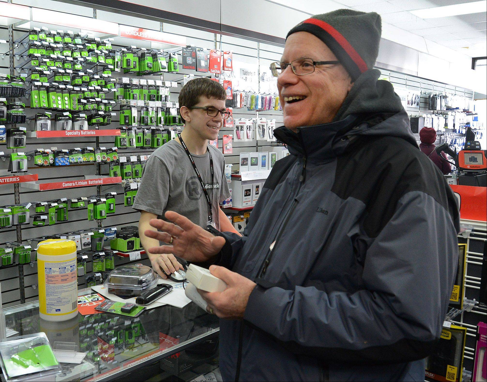 Roger Kalisiak of Hoffman Estates inquires about the Jabra In-Car Speakerphone at the Arlington Heights Radio Shack. Suburban electronics and telecommunications stores report brisk sales of Bluetooth devices since talking on a cellphone behind the wheel without a hands-free device became illegal in Illinois on New Year's Day.