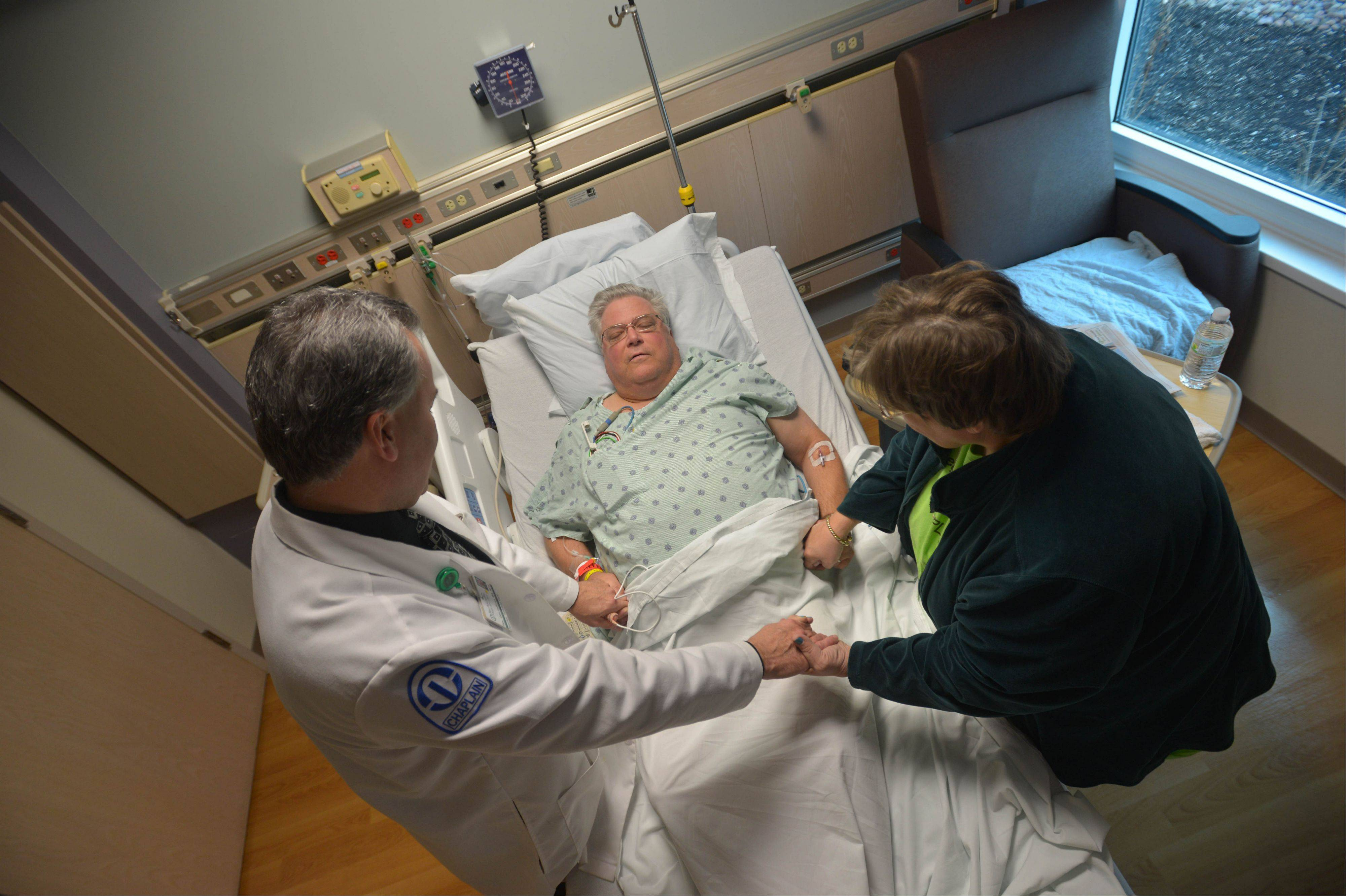 Dan Sullivan takes a moment to pray with Charles Sondgeroth and his wife Joanna of Sandwich during a recent hospitalization at Rush-Copley Medical Center in Aurora.
