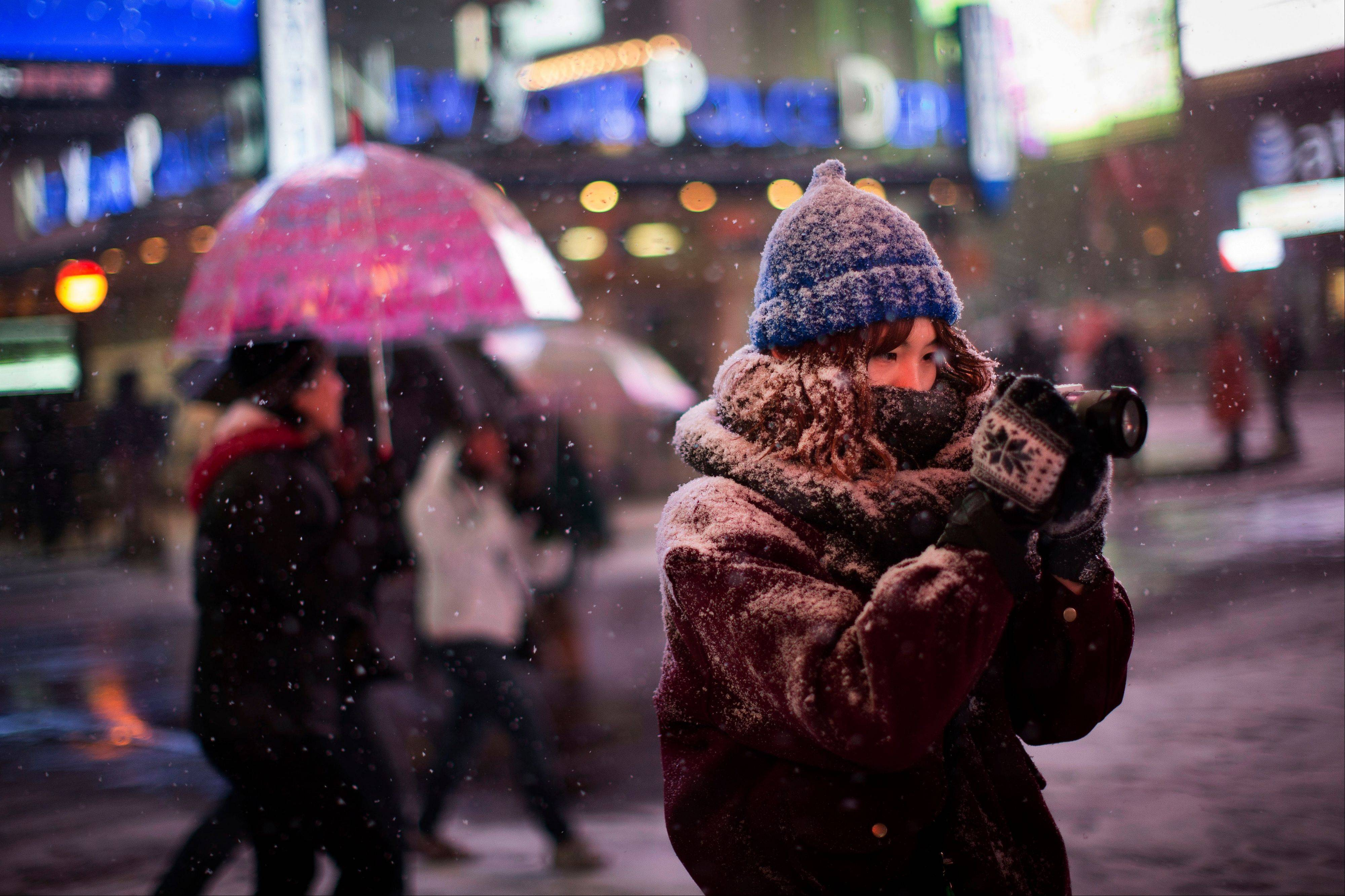 A pedestrian takes a photograph under falling snow in Times Square, Thursday, Jan. 2, 2014, in New York. The storm is expected to bring snow, stiff winds and punishing cold into the Northeast.