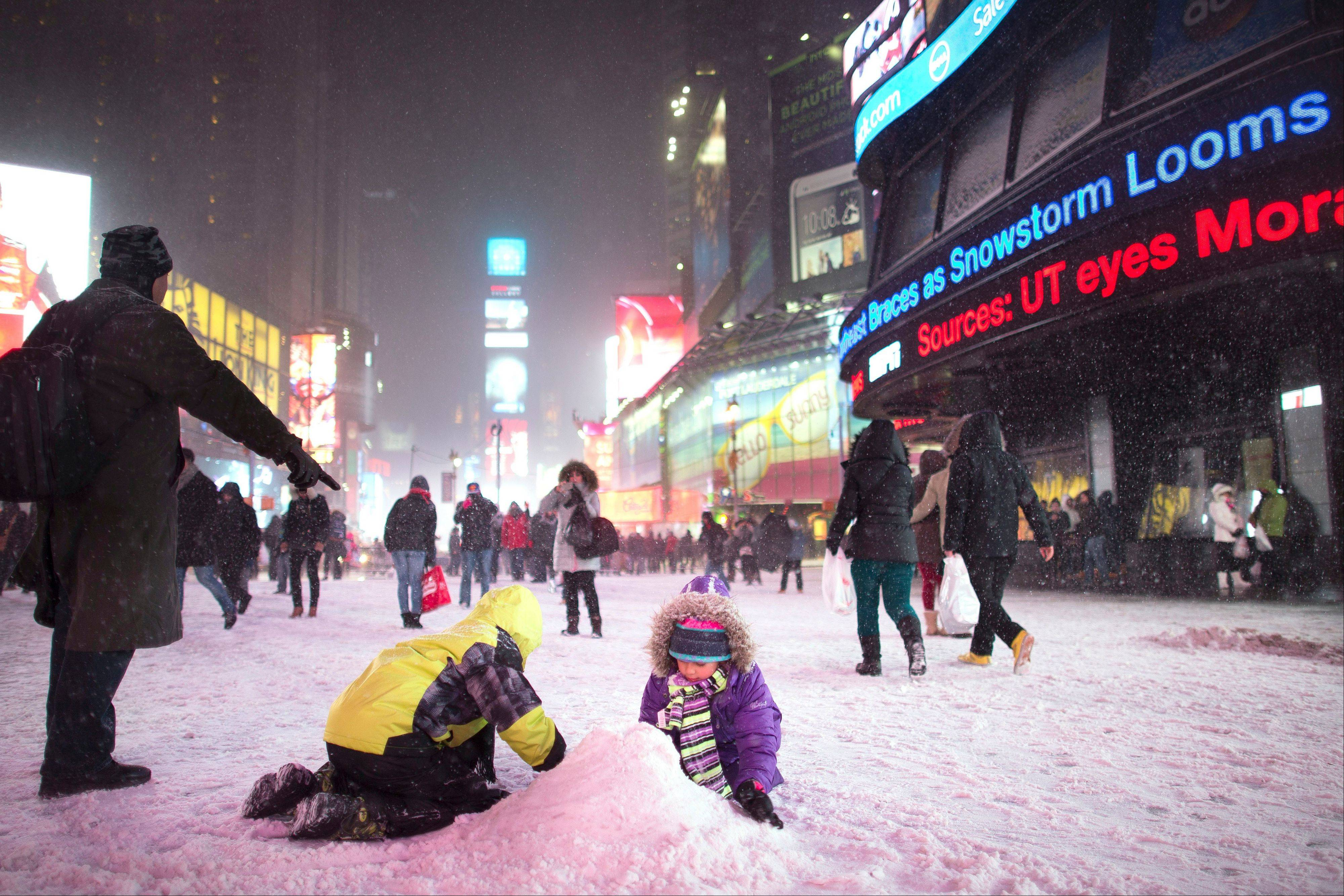 Children make a snow pile in Times Square, during a snowstorm, Thursday, Jan. 2, 2014, in New York. The storm is expected to bring snow, stiff winds and punishing cold into the Northeast.