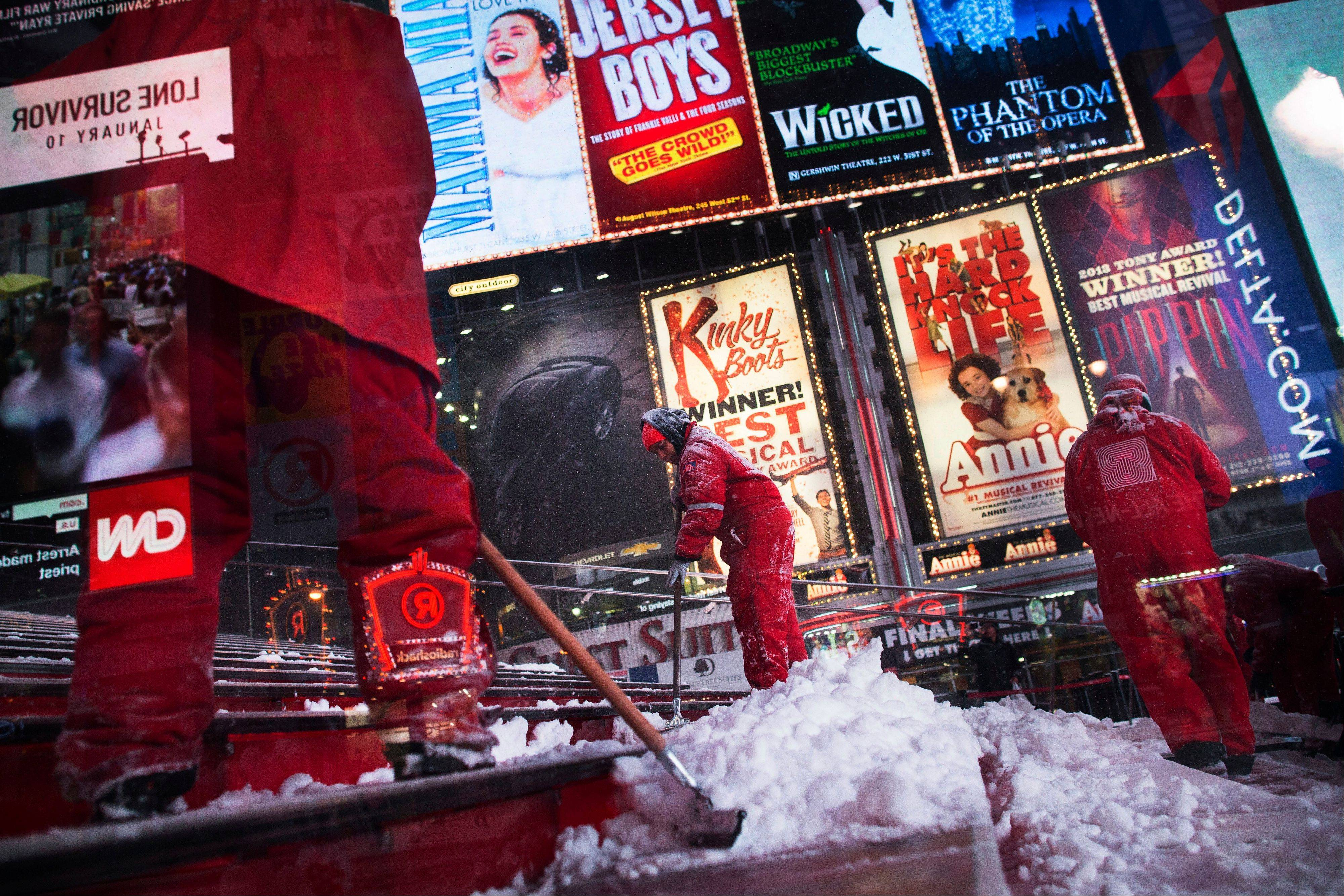 Workers clean snow from the steps of TKTS Times Square ticket booth, Thursday, Jan. 2, 2014, in New York. The storm is expected to bring snow, stiff winds and punishing cold into the Northeast.