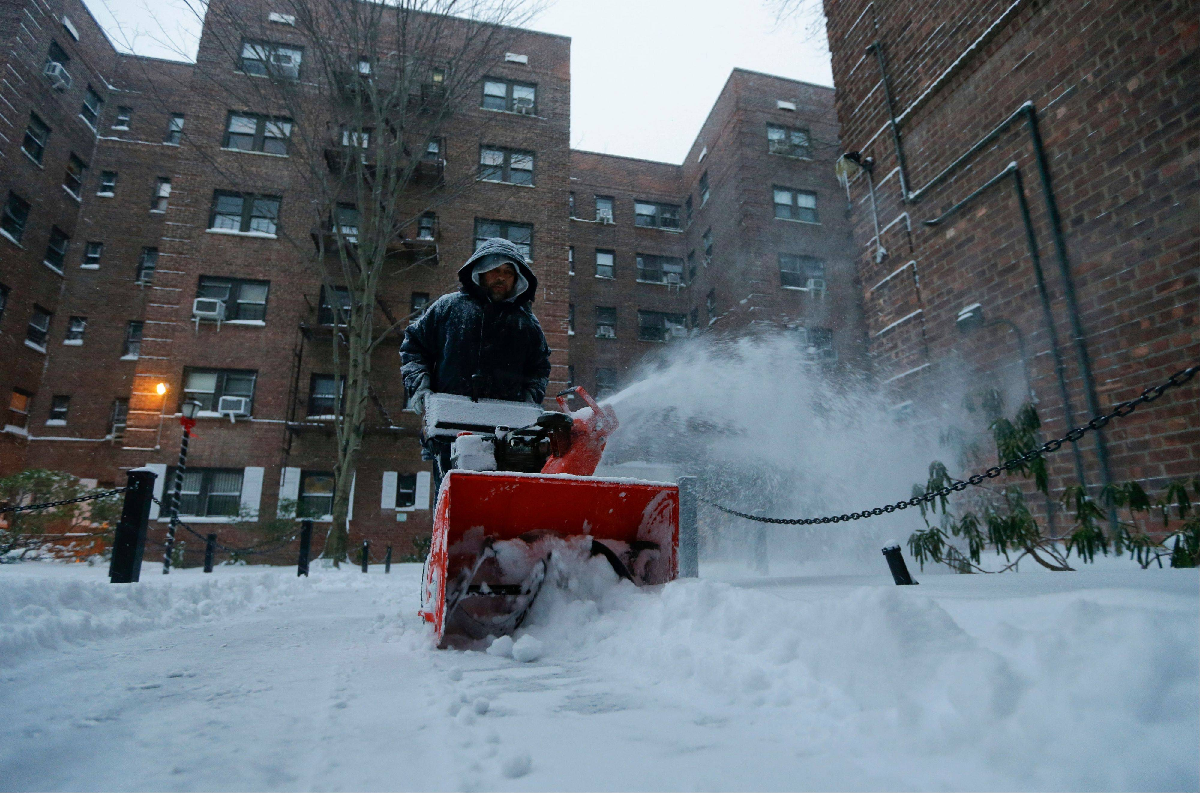 A man who did not wish to be identified uses a snowblower to clear a path near an apartment complex Friday, Jan. 3, 2014, in the Queens borough of New York. The New York City Office of Emergency Management issued a hazardous travel advisory into Friday, warning that roads likely would be icy and snow would continue to drift.