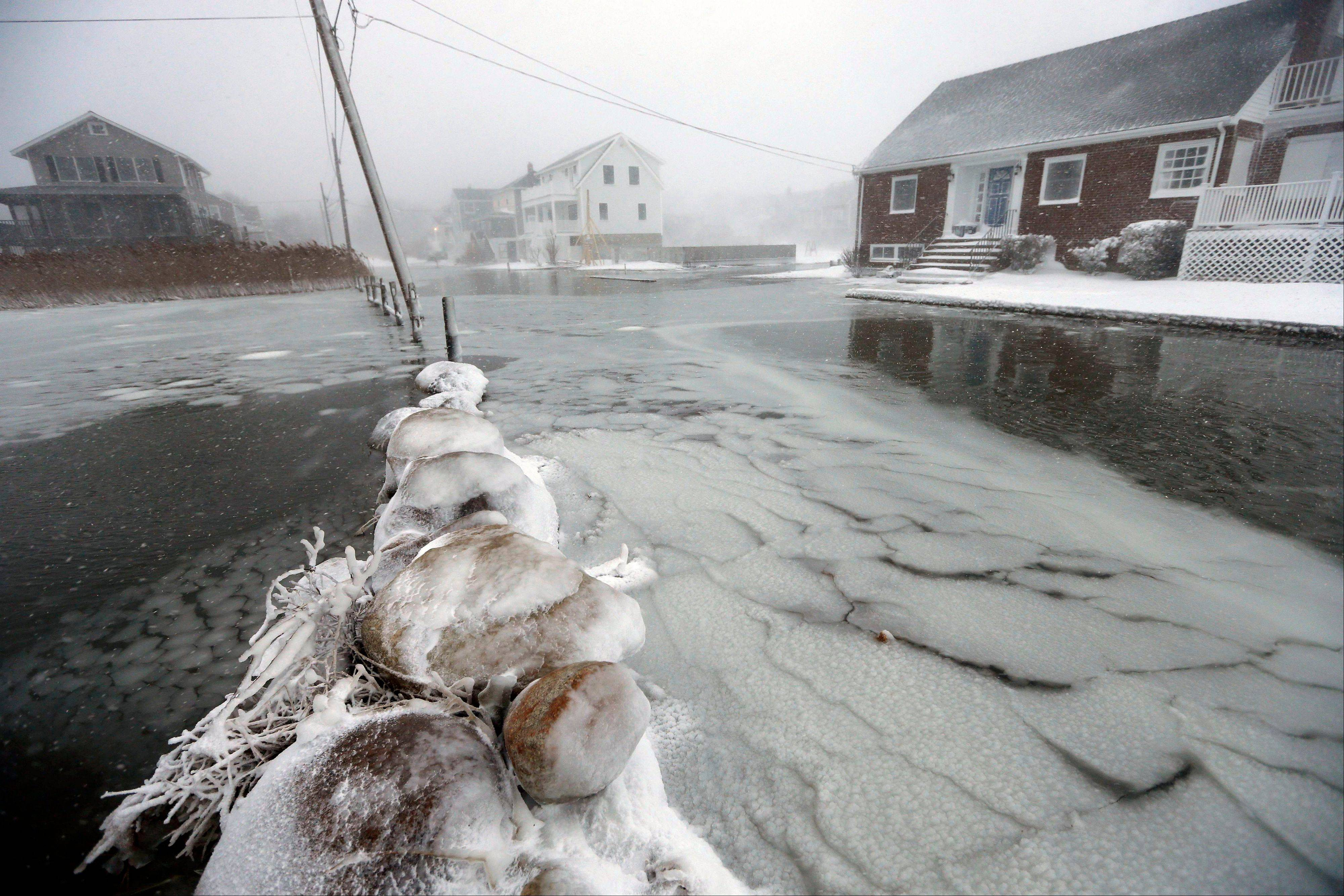Houses line a flooded street along the shore in Scituate, Mass., Friday, Jan. 3, 2014. A blustering winter storm that dropped nearly 2 feet of snow just north of Boston, shut down major highways in New York and Pennsylvania and forced U.S. airlines to cancel thousands of flights nationwide menaced the Northeast on Friday with howling winds and frigid temperatures.