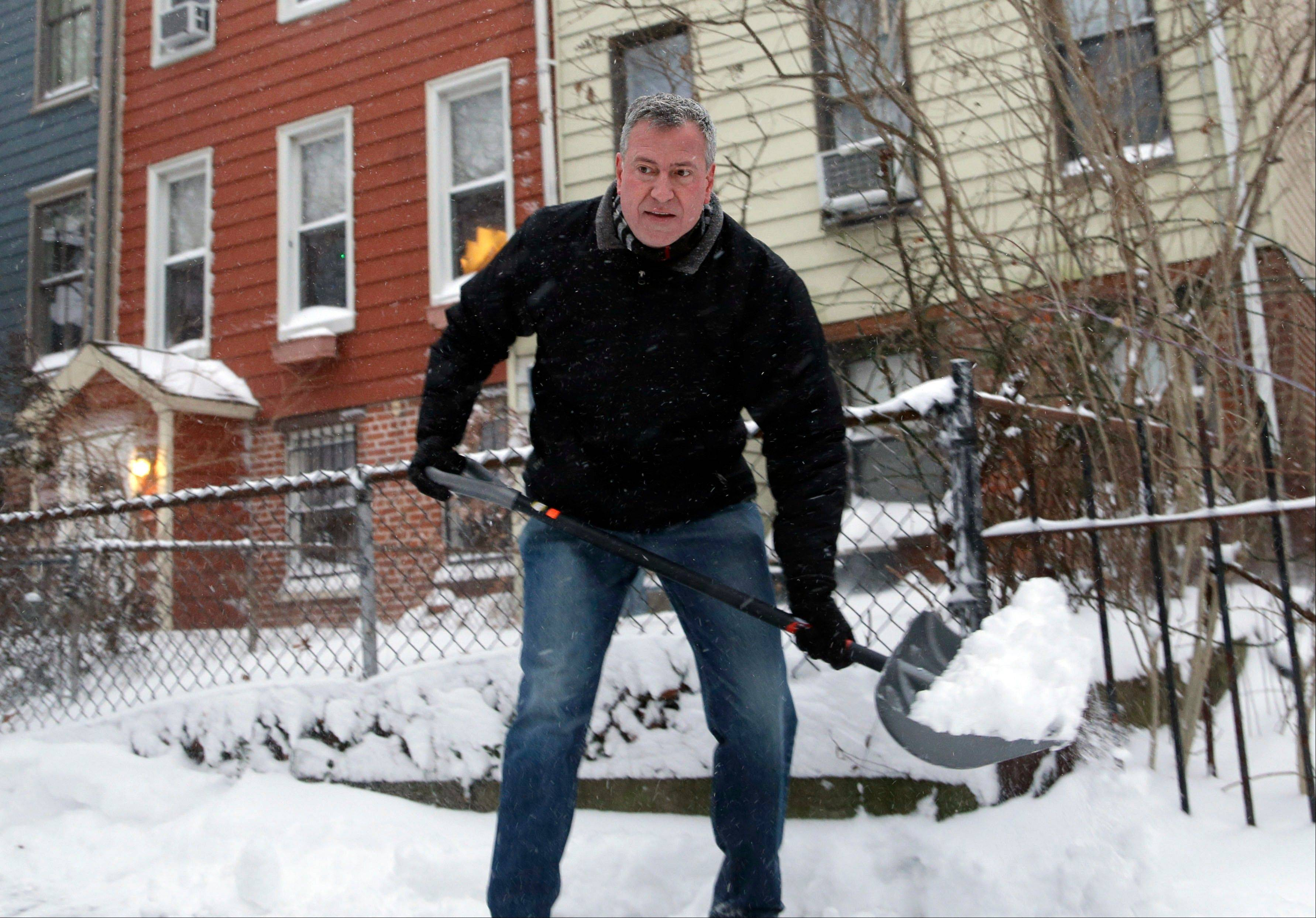 New York City Mayor Bill de Blasio shovels the sidewalk in front of his house in New York, Friday, Jan. 3, 2014. New York City public schools were closed Friday after up to 7 inches of snow fell by morning in the first snowstorm of the winter, and it the first test for the new mayor hours after he was sworn in.