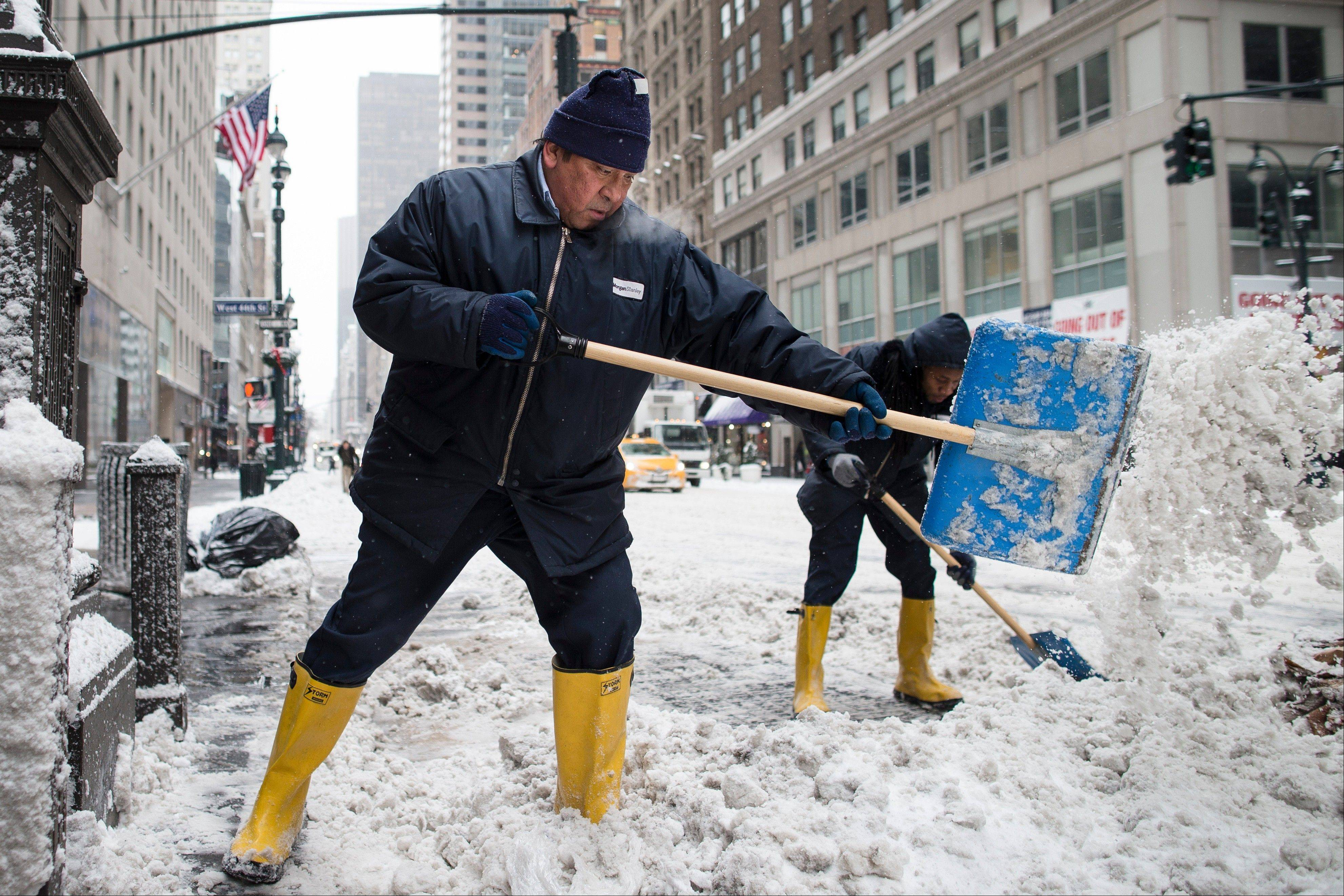Workers clear sidewalks of snow on Fifth Avenue, Friday, Jan. 3, 2014, in New York. New York City public schools were closed Friday after up to 7 inches of snow fell by morning in the first snowstorm of the winter.