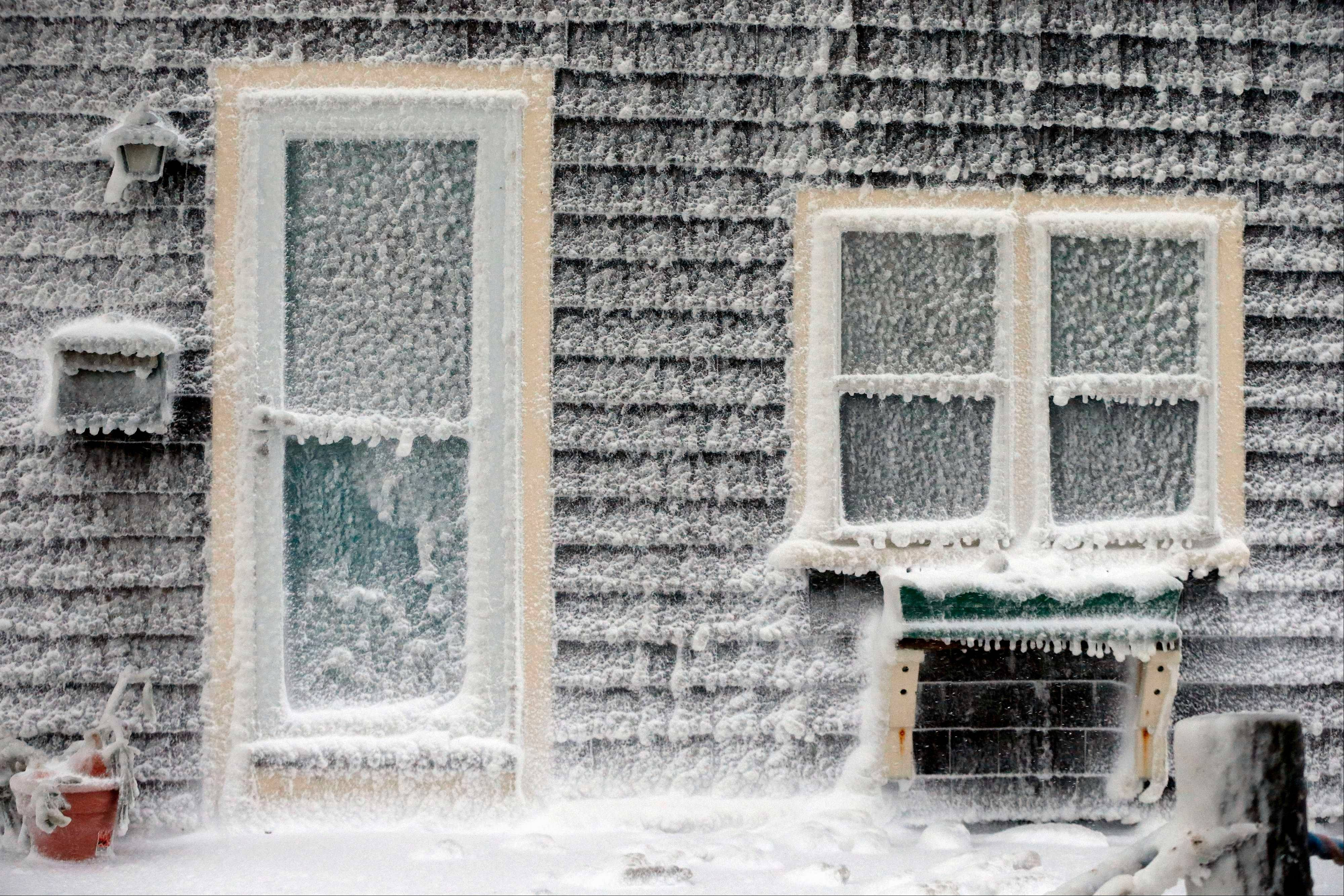 Ice from breaking waves coats a house along the shore in Scituate, Mass., Friday, Jan. 3, 2014. A winter storm slammed into the U.S. Northeast with howling winds and frigid cold, dumping nearly 2 feet of snow in some parts and whipping up blizzard-like conditions Friday.